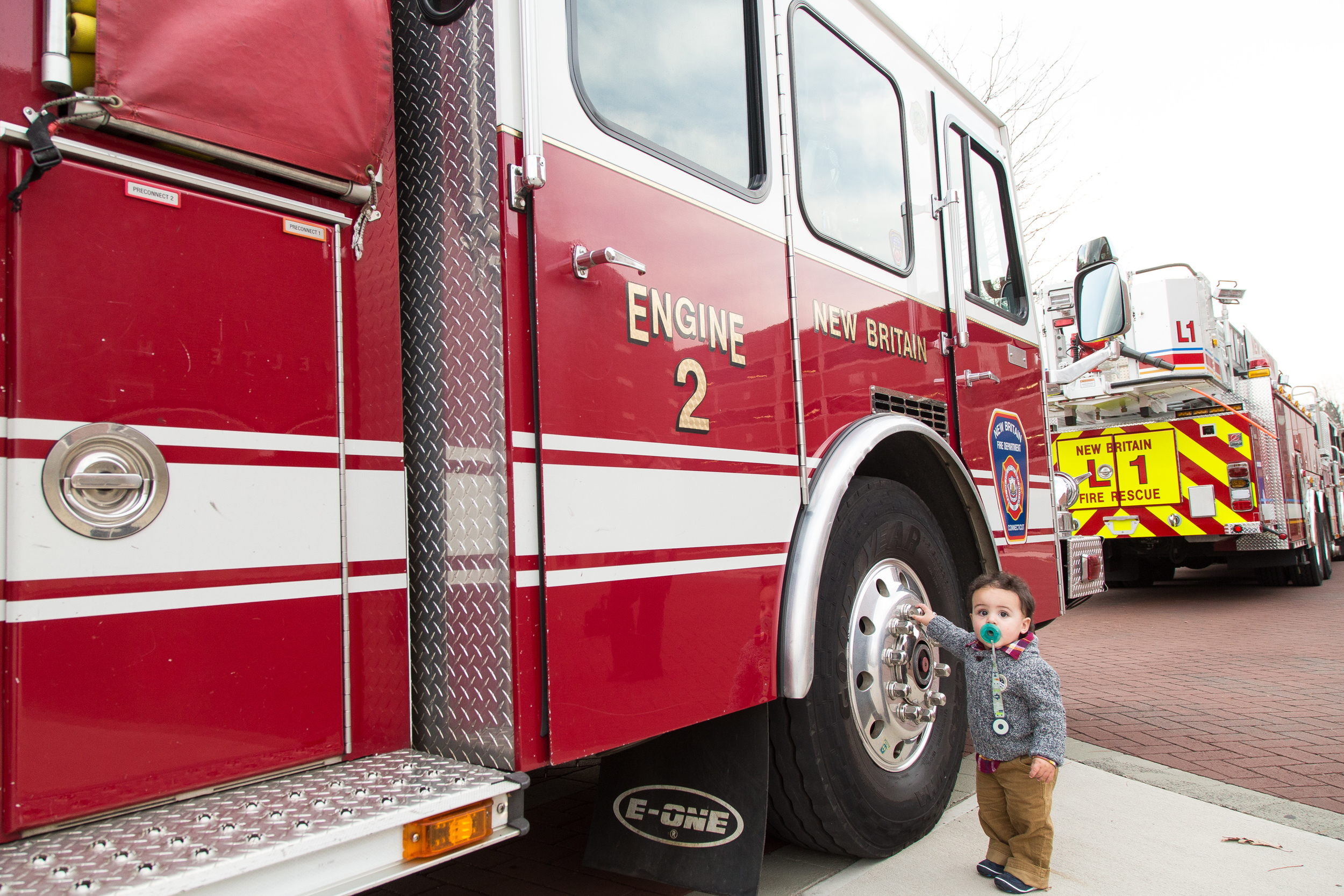 A young boy explores a fire truck in New Britain during a Fire Academy graduation.