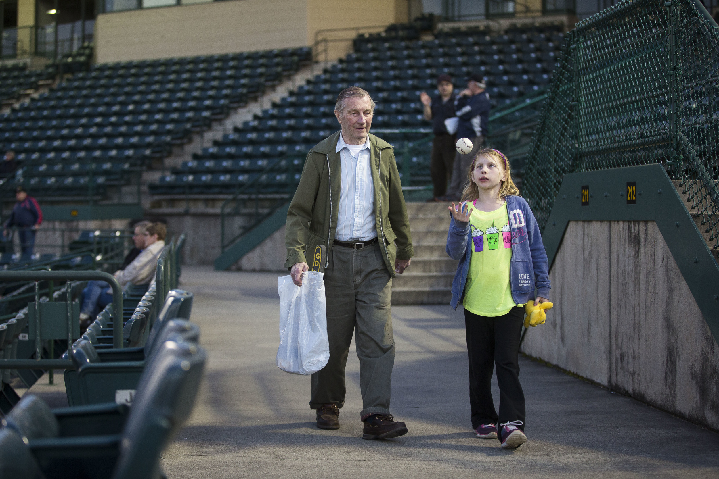 A girl and her grandfather walk during a NB Bees game.