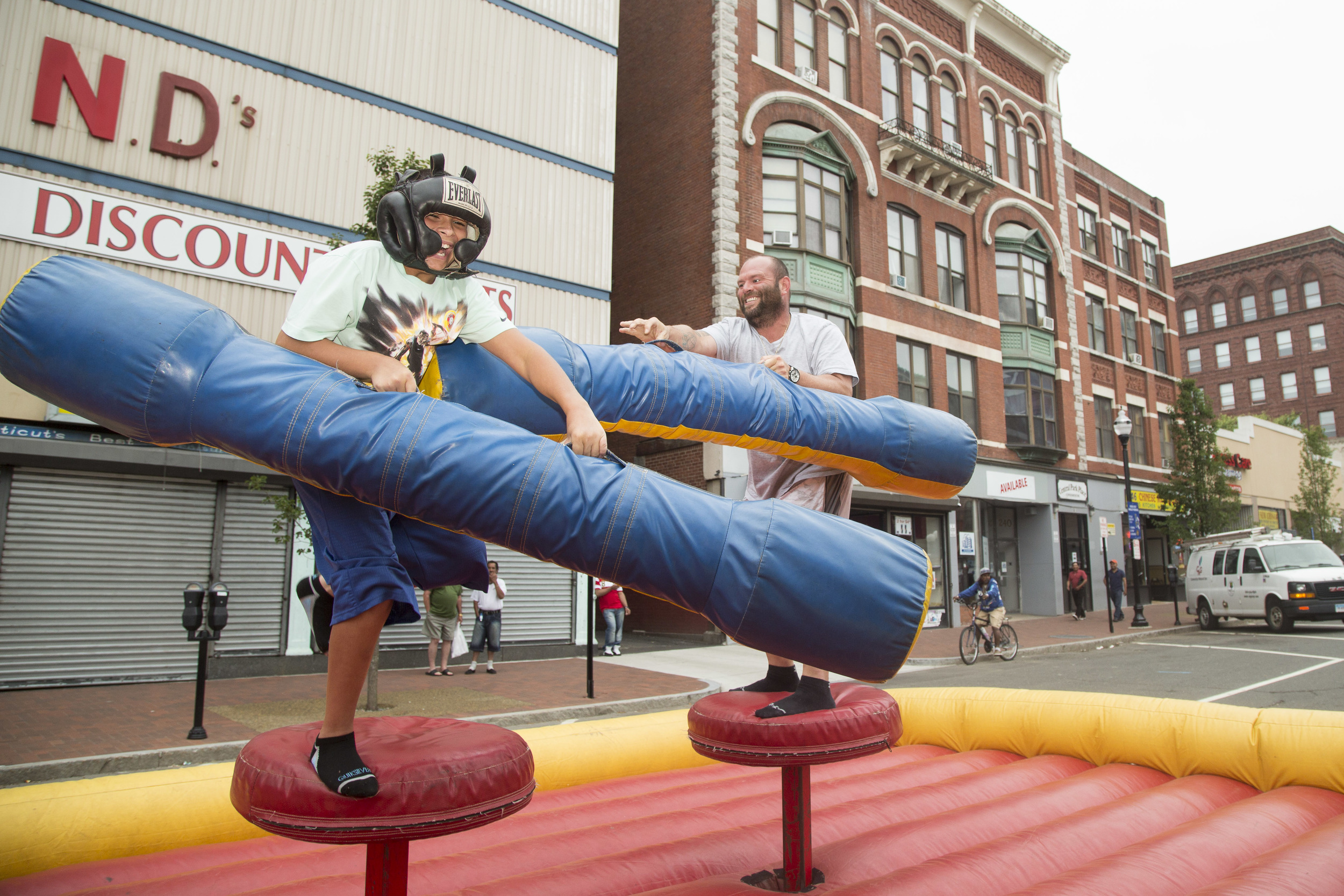 Elvin Rios knocks his son, Johnny Rosario, off an inflatable game in New Britain.