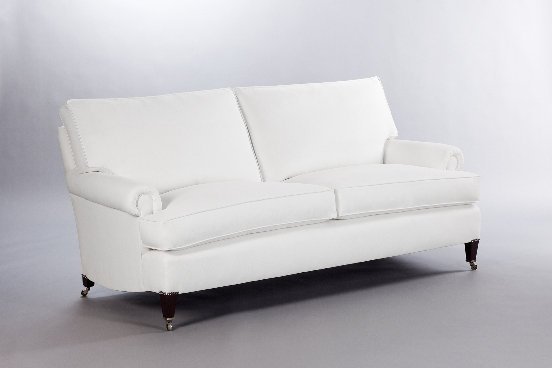 The quintessential English Arm sofa by George Smith; this version has a T-cushion and tapered legs with casters.