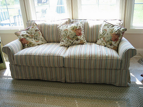 A skirted sofa with two pleats, rolled arms, and a straight cushion.
