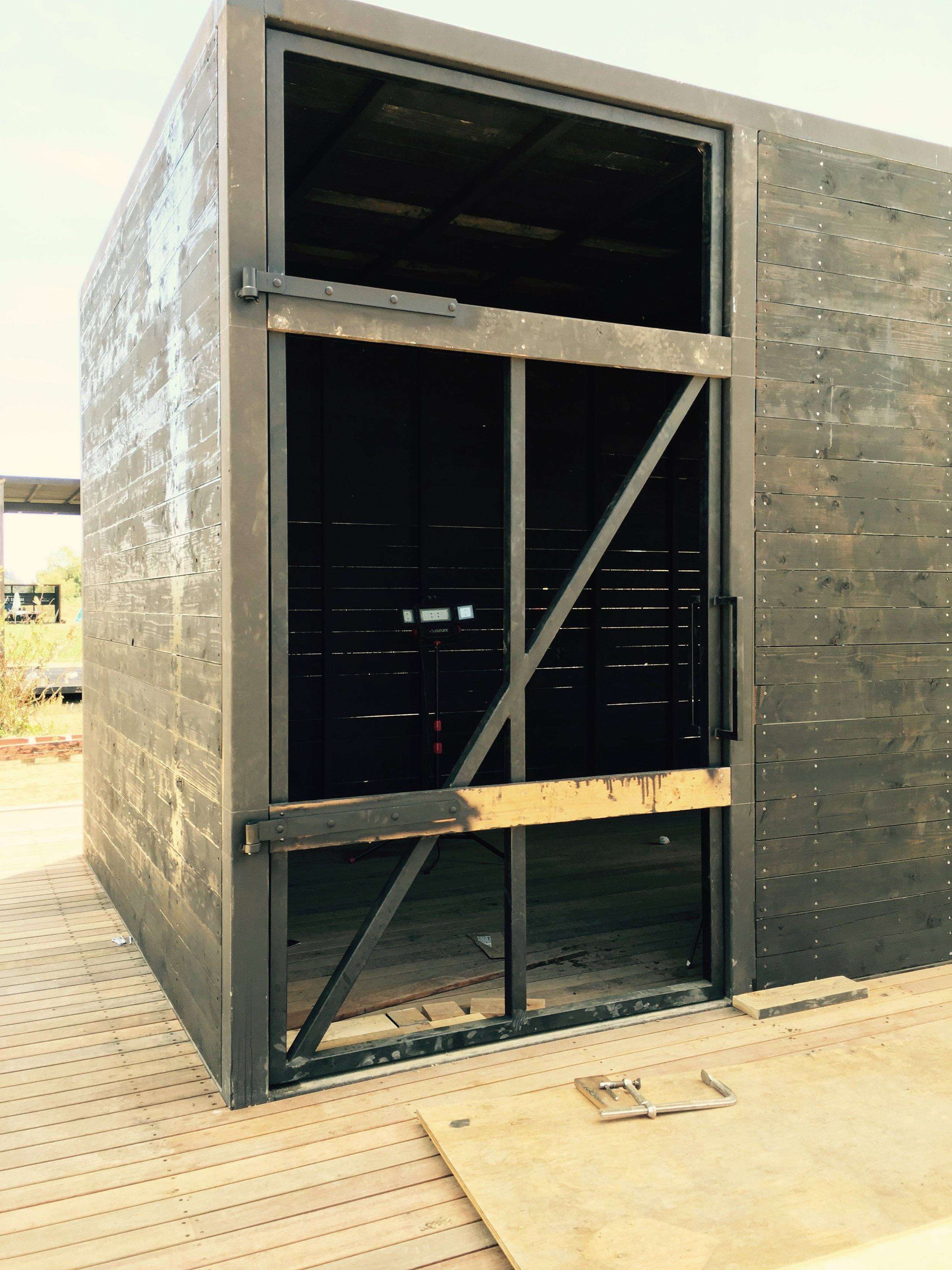We are fabricating our own metal and wood doors for all the buildings. This one is a prototype for all the Ag Buildings. It will be on the chicken barns and other buildings. 5' wide x 10' tall. 150 lbs. Finished in Douglas Fir and Black Pine Tar. The door in the photo isn't complete.