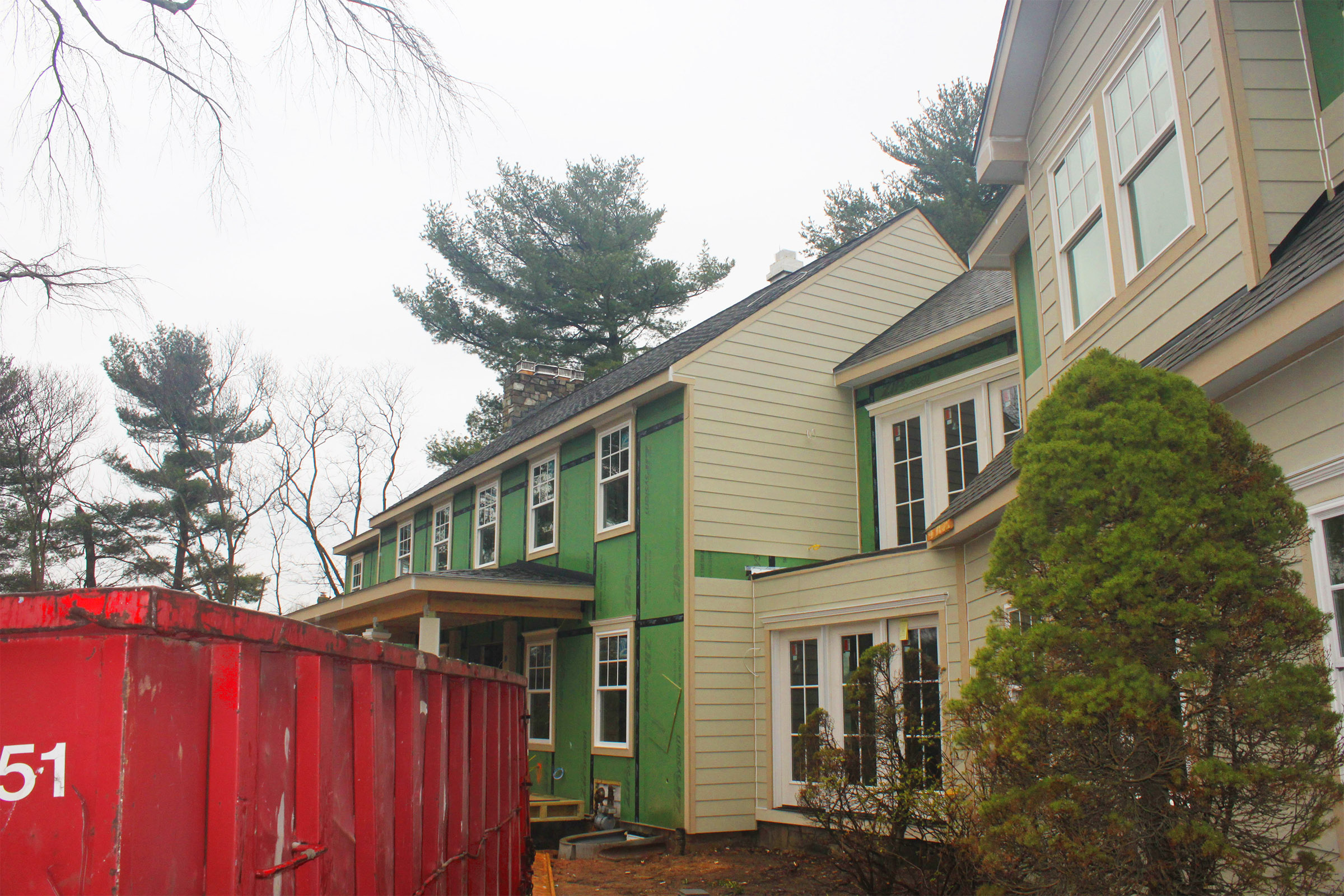 Exterior wall in process of adding siding. The green panels are ZIP sheathing with integrated water barrier.