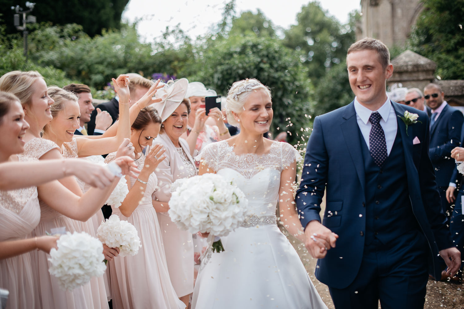 wedding guests throwing confetti over the bride and groom in Stamford