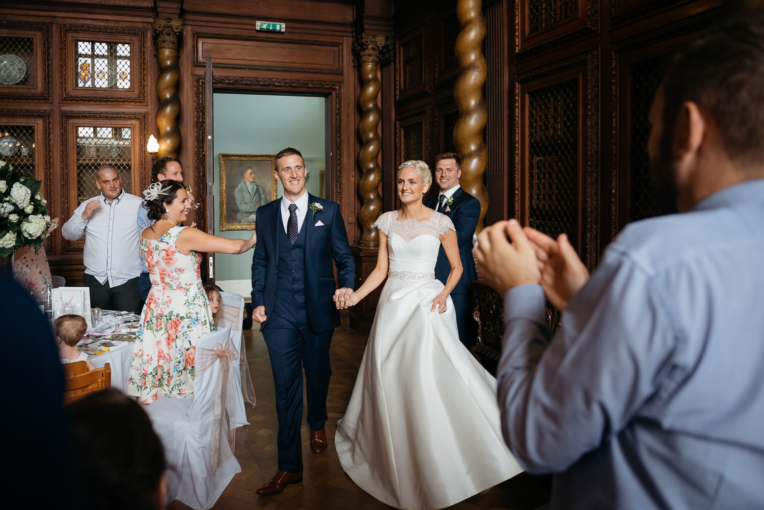 bride and grrom enter the great hall at burghley house