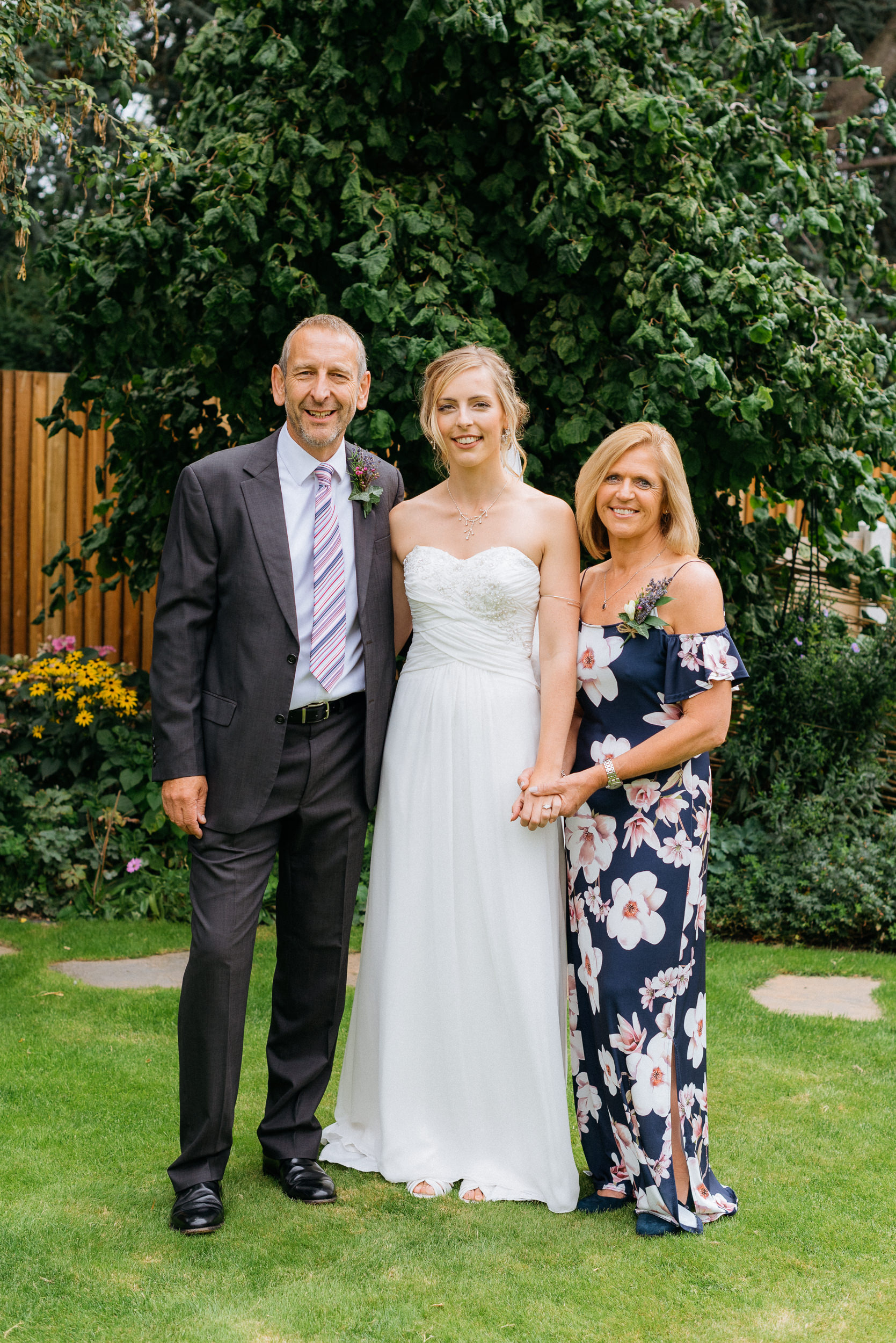 A photograph of the bride with her mother and father