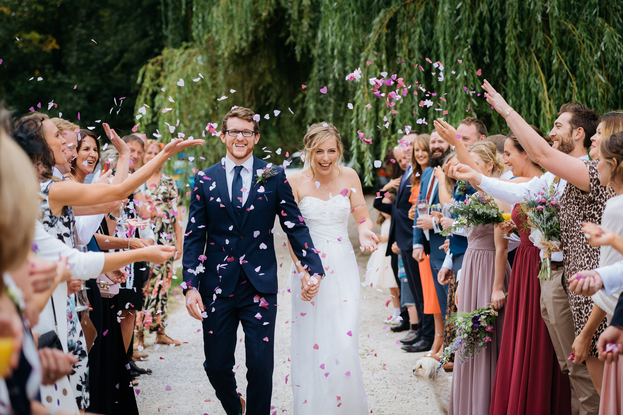 bride and groom have confetti thrown over them at Risley Hall