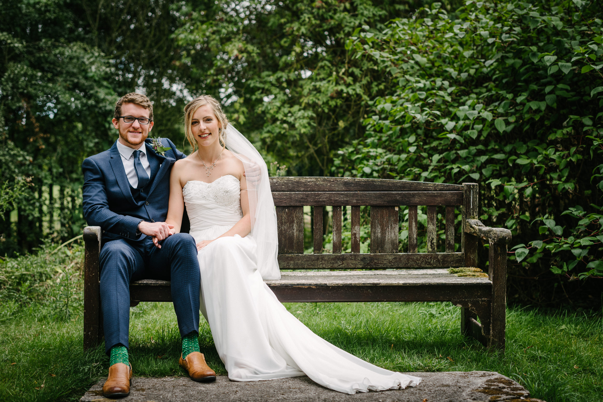 bride and groom on the bench at Risley Hall