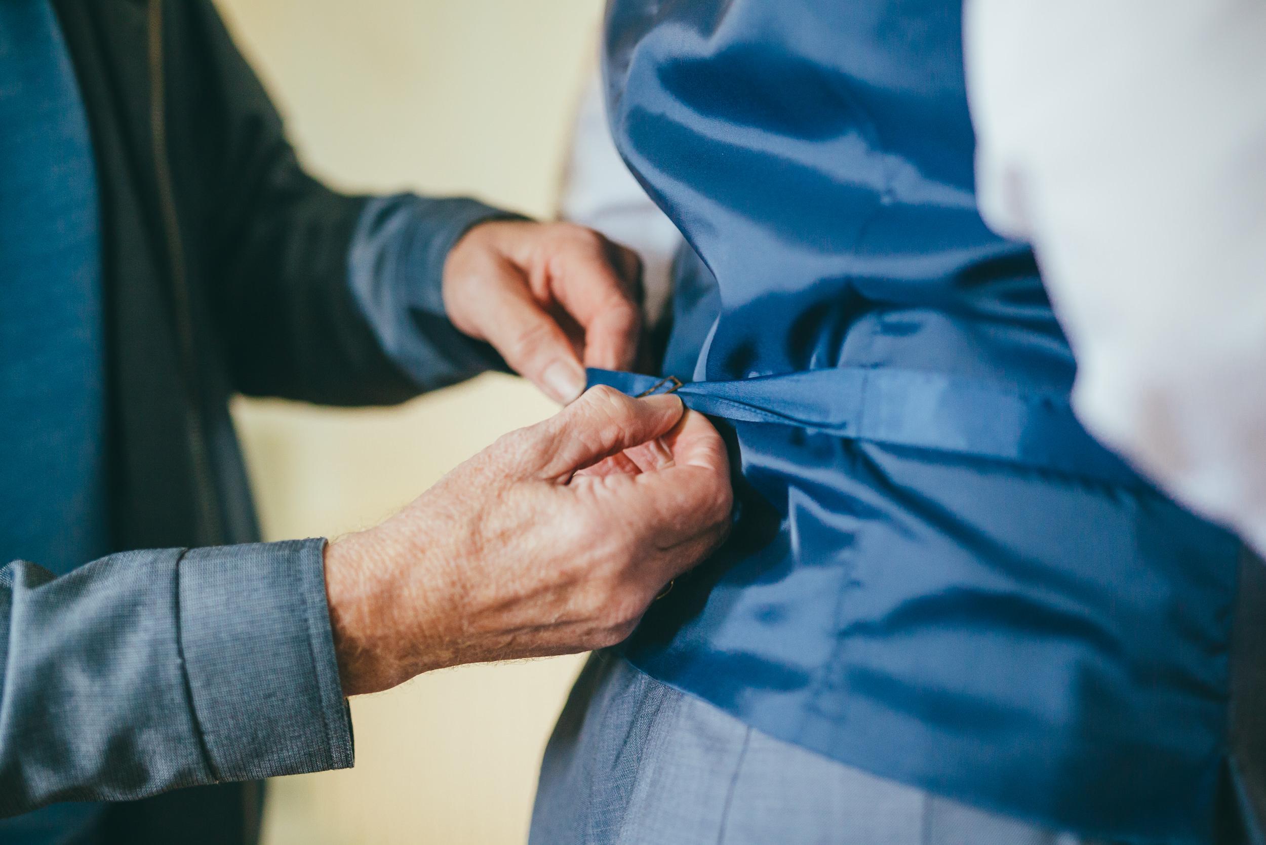 Groom putting on his waistcoat