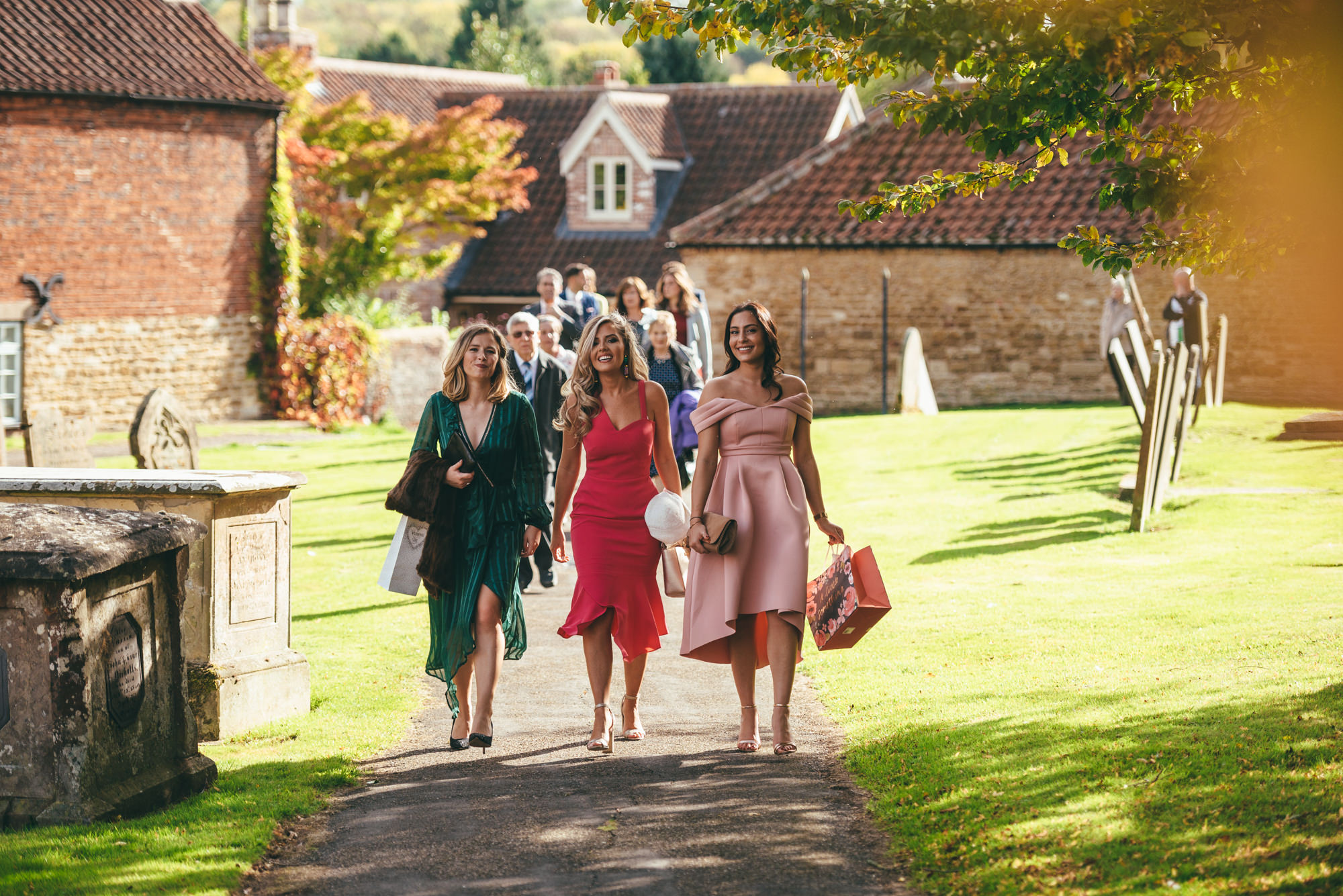 female wedding guests arrive at church
