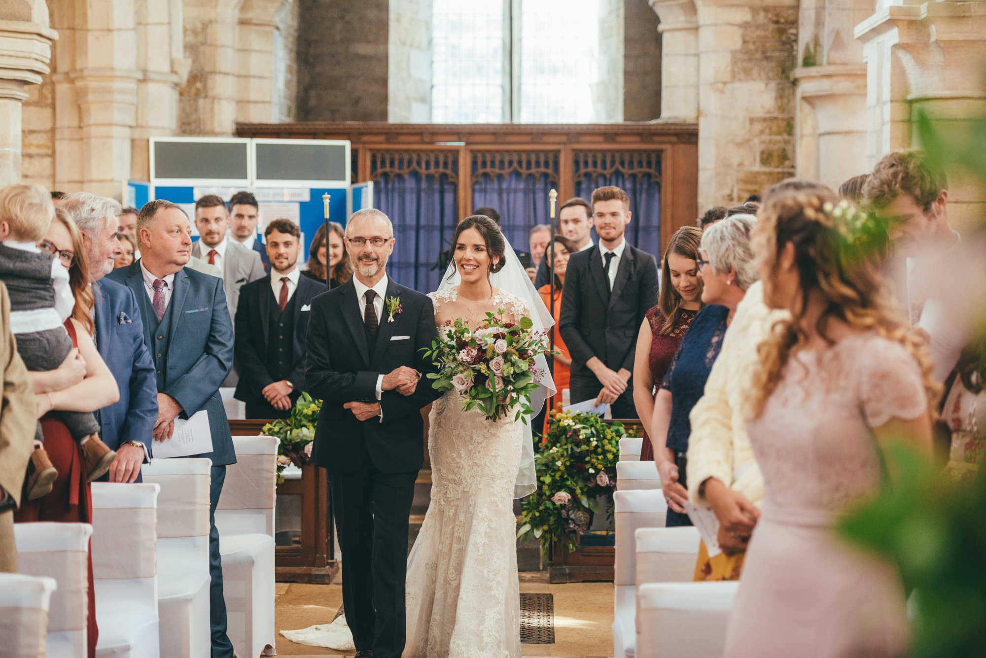 bride and her father walking down the aisle at harlaxton church