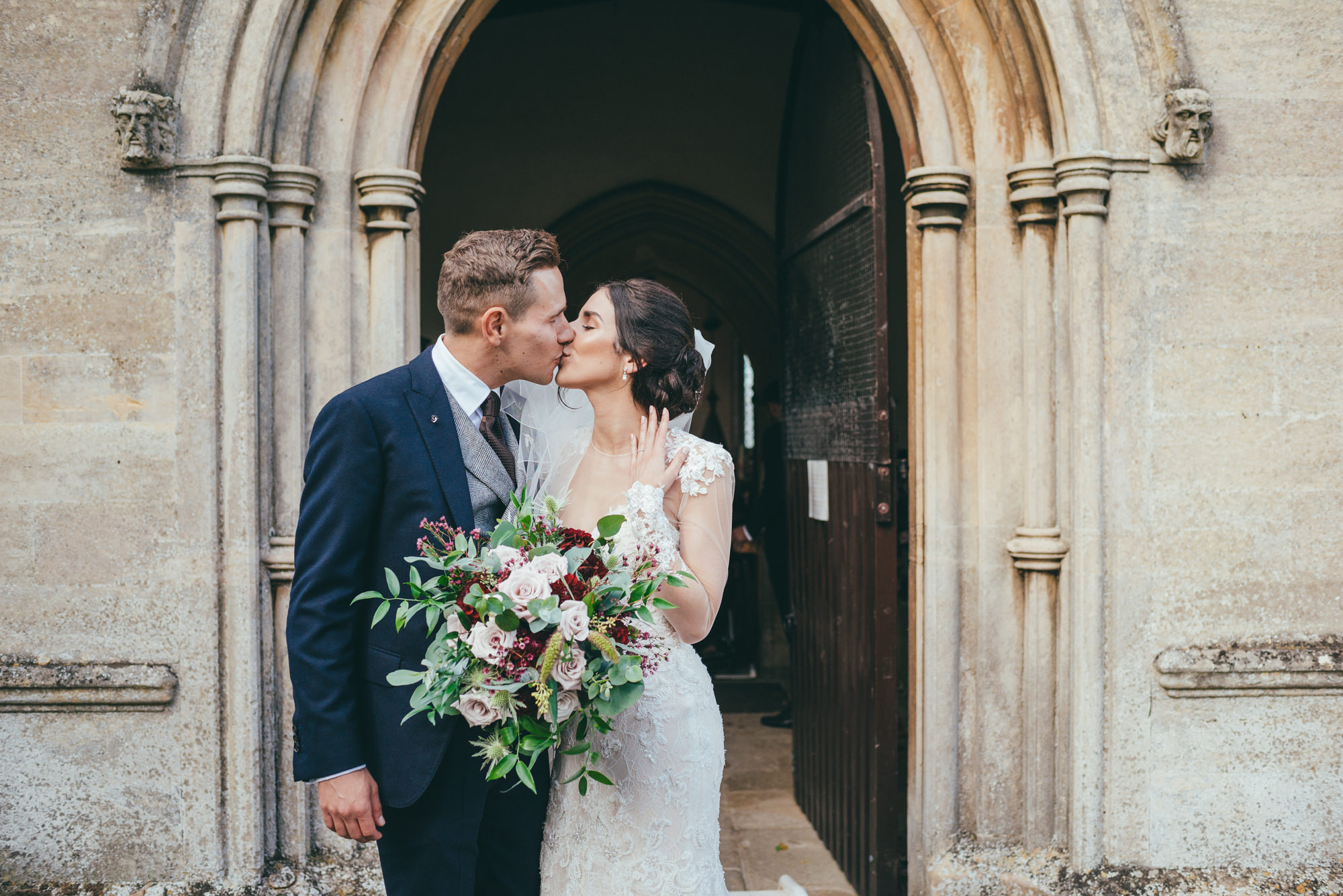 bride and grrom kiss outside of harlaxton church