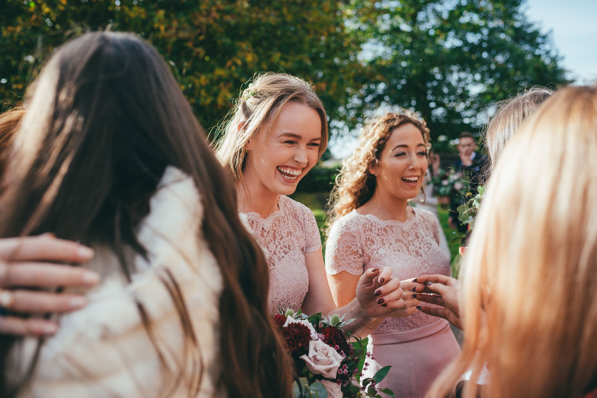 bridesmaids share a joke with the wedding guests