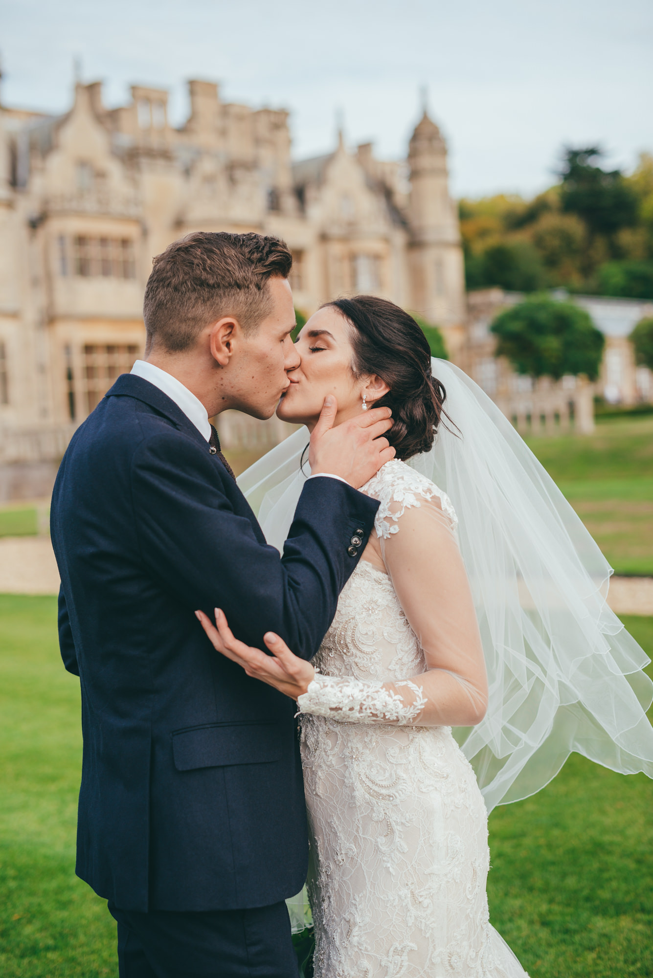 bride and groom kissing on the lawns at harlaxton manor