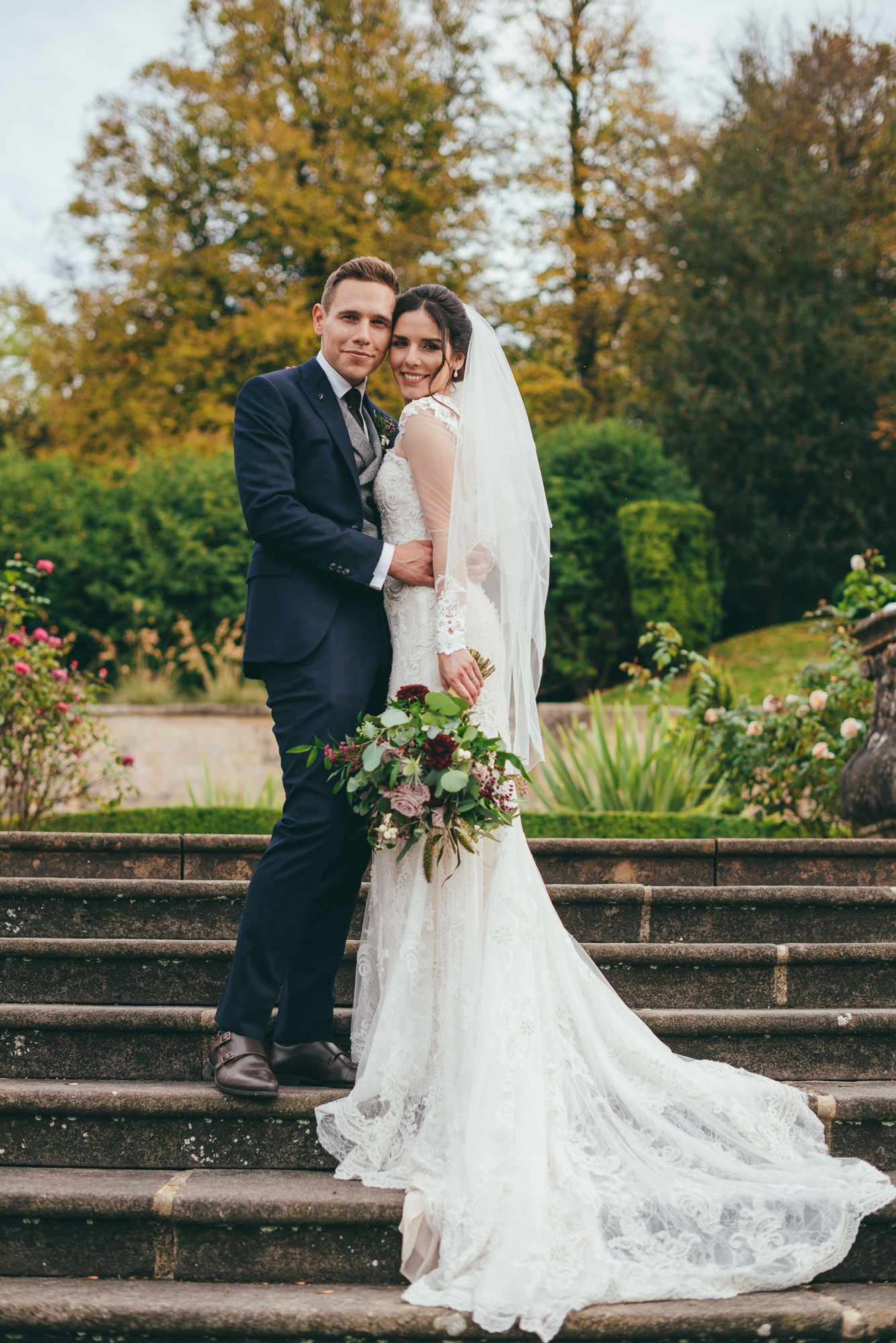 posed picture of the bride and groom on the steps at harlaxton manor