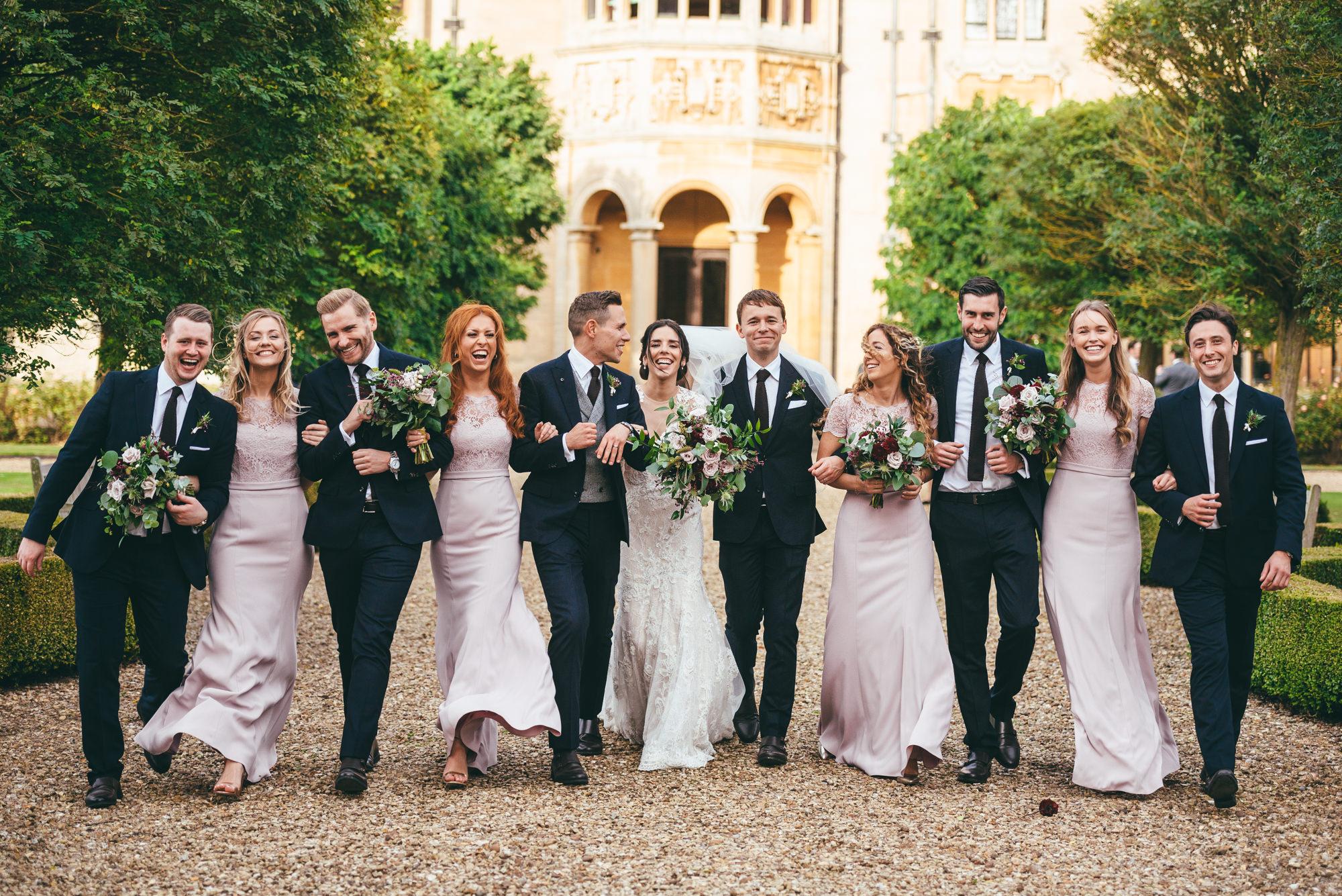 bridal party walking together laughing at harlaxton manor