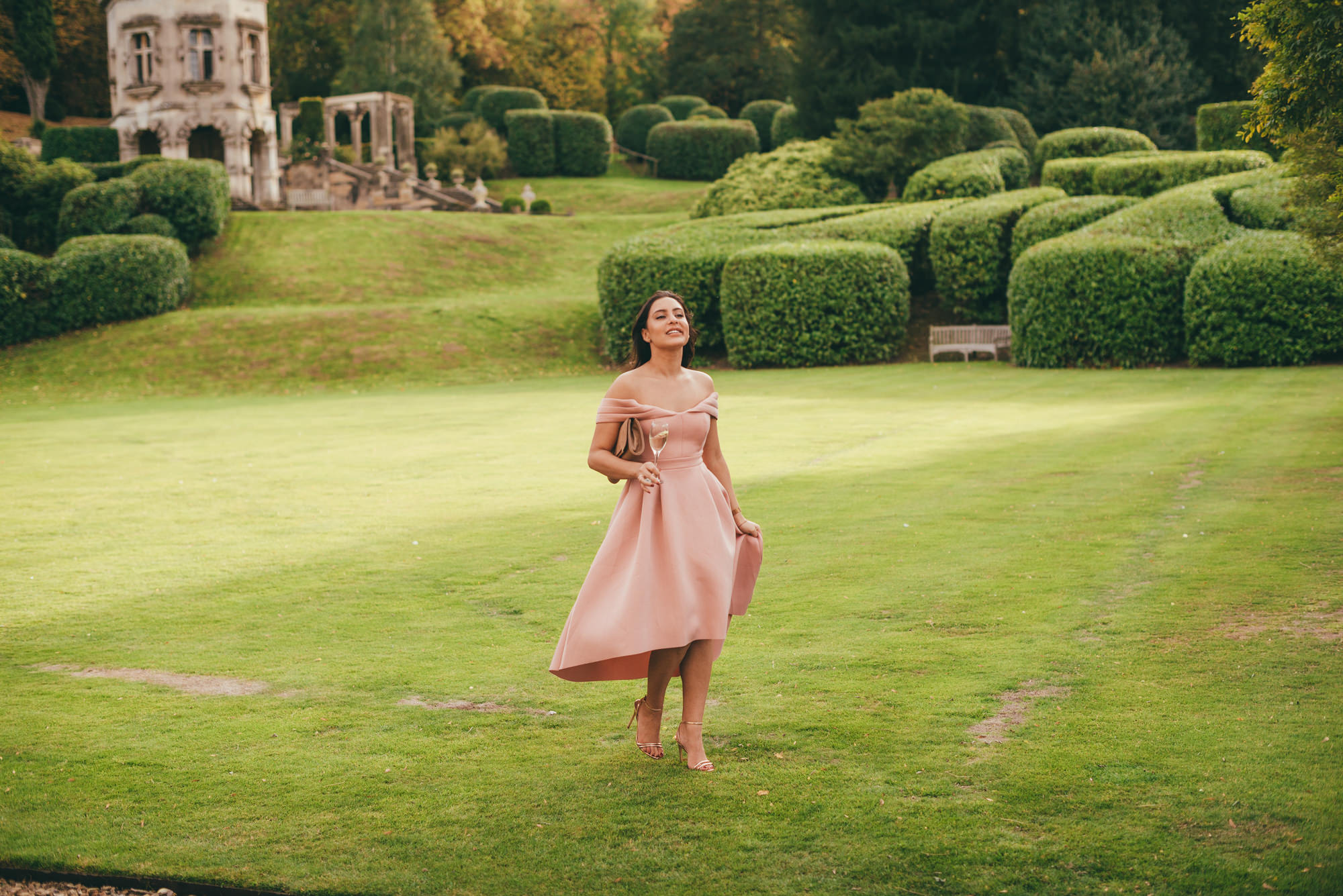 wedding guests walking across the lawn at harlaxton manor