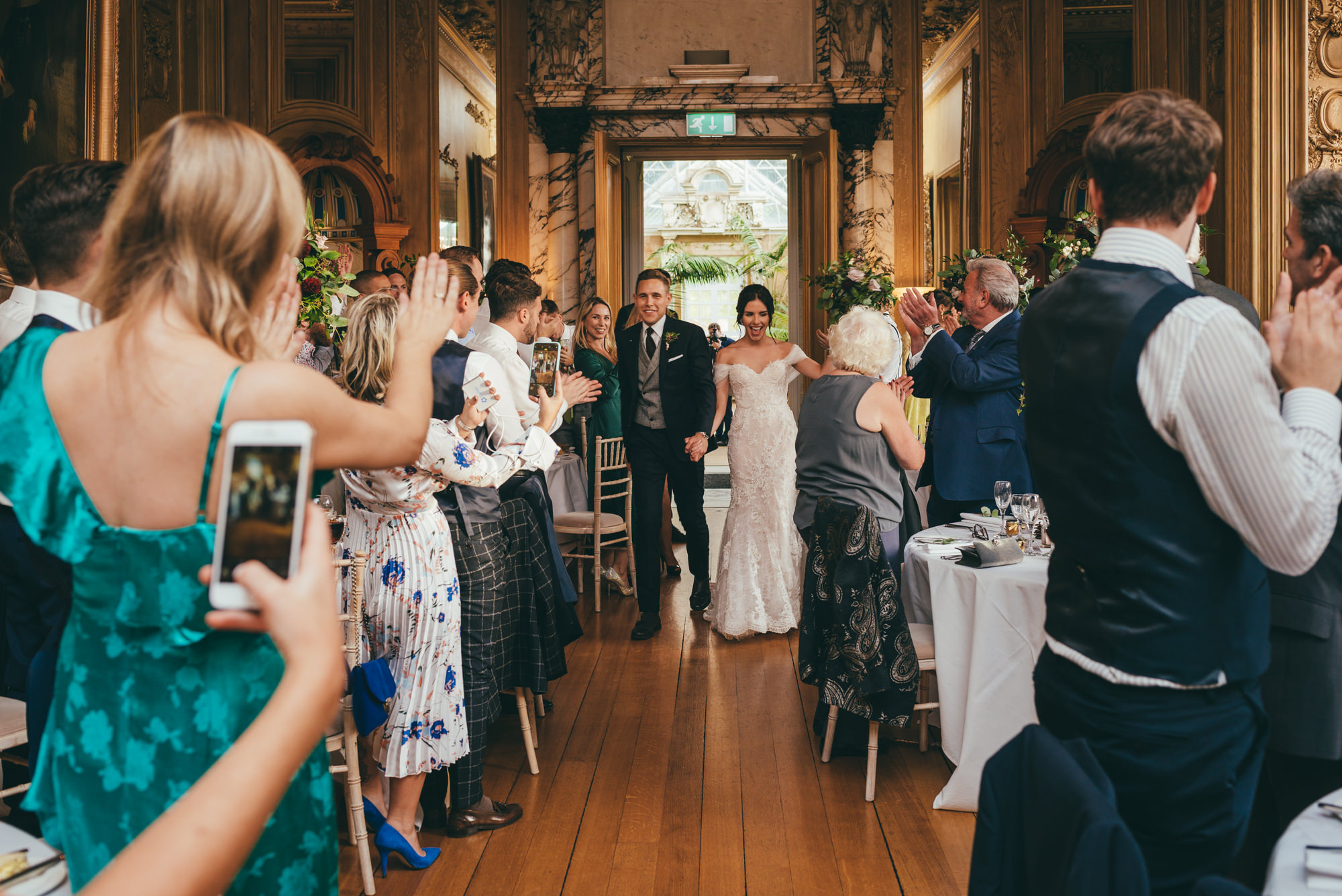 bride and groom enter the reception room as mr and mrs