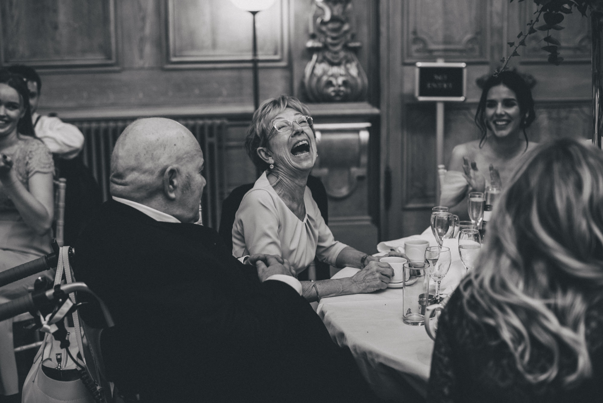 grooms mother laughing at the wedding speeches