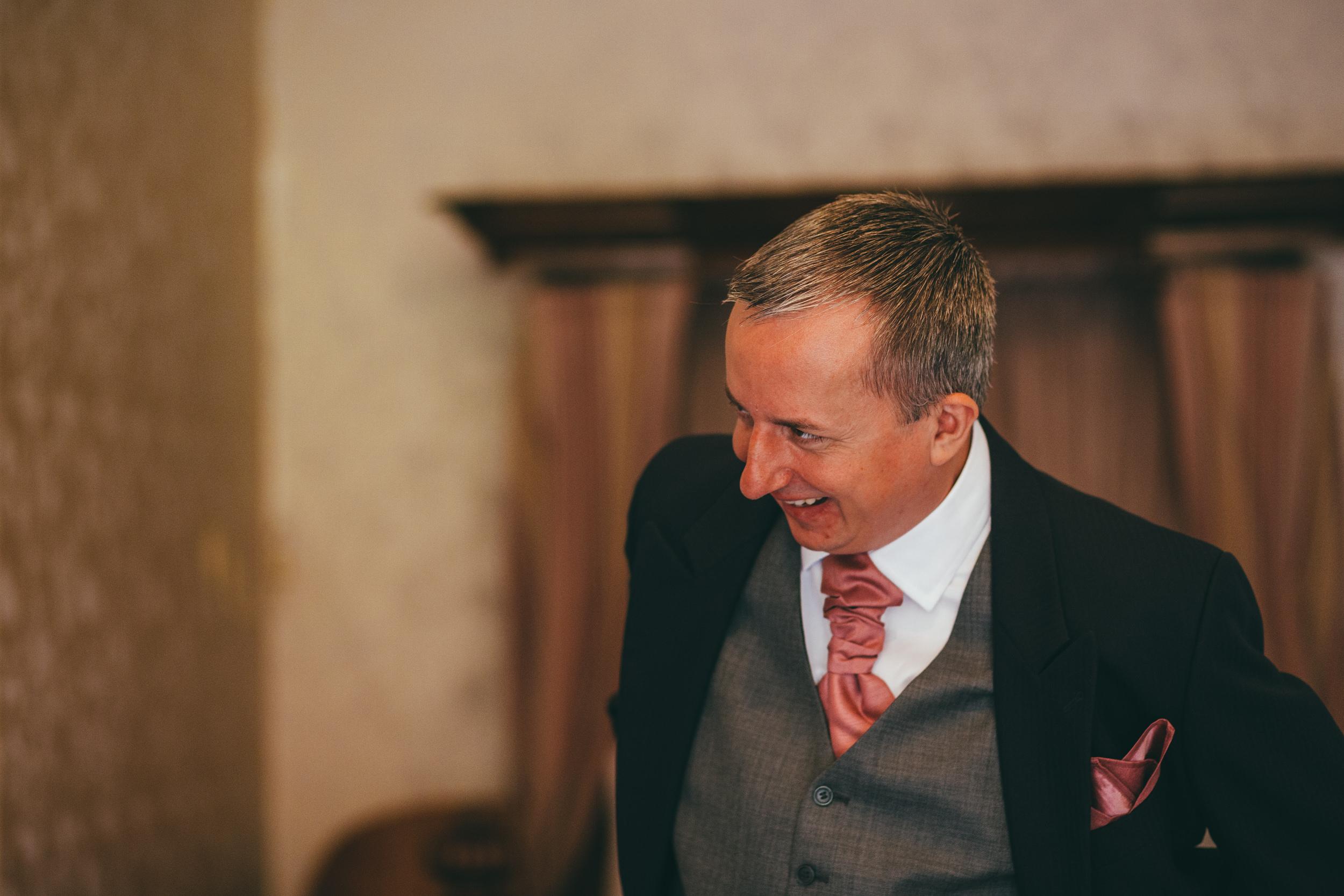Groomsman laughing at Harlaxton Manor wedding