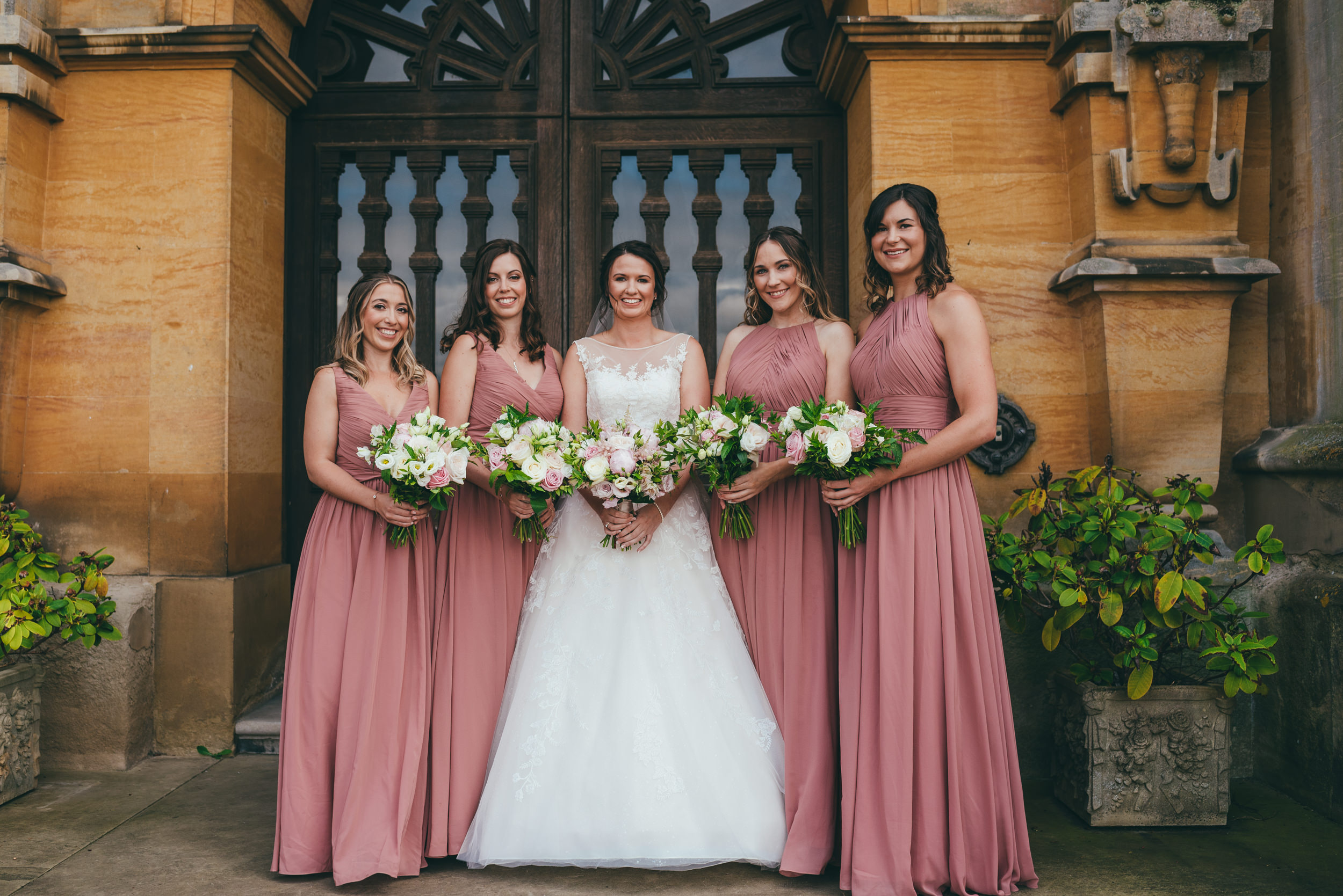 The bride and her bridesmaids at the front door at Harlaxton Manor