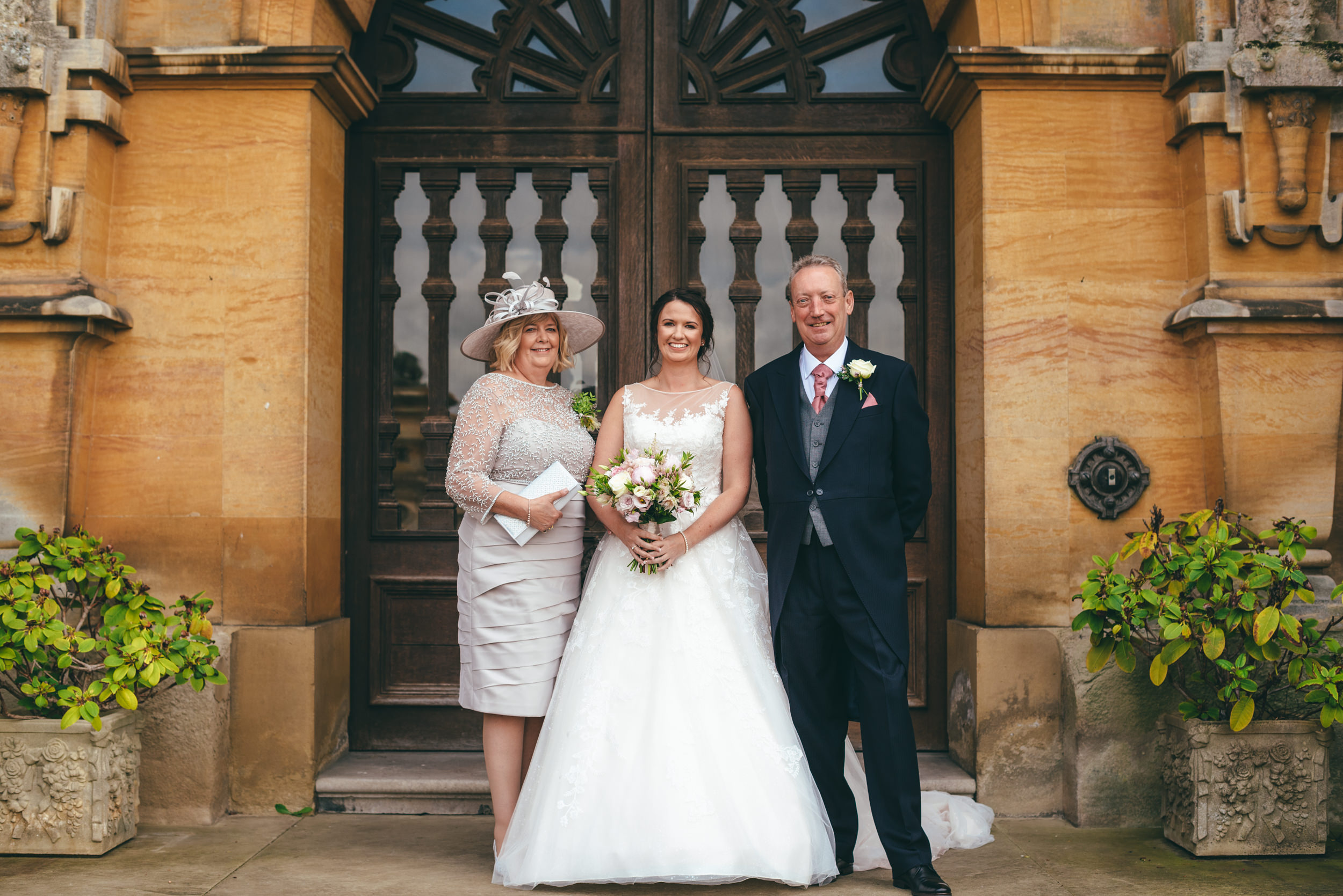 A photograph of the Bride and her parents at her wedding at Harlaxton Manor