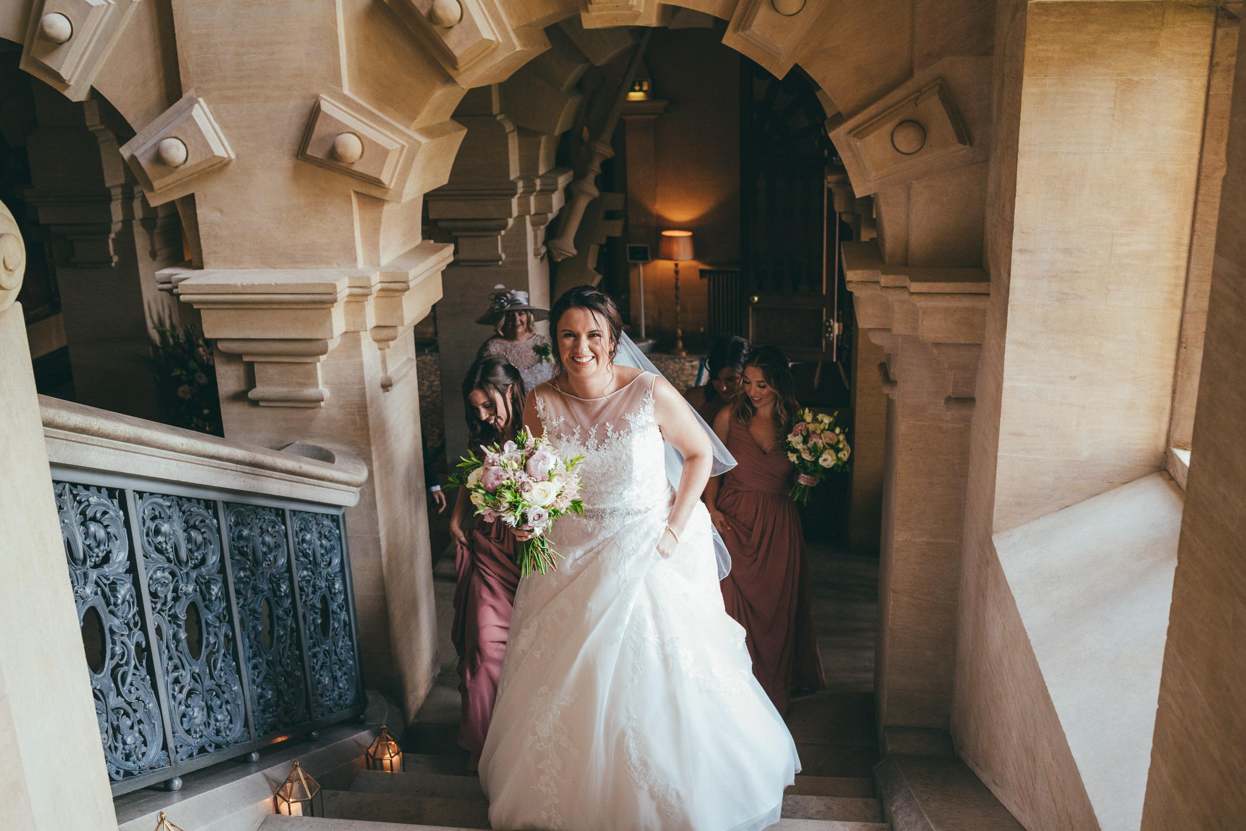 Bride walking up the stairs to get married at Harlaxton Manor