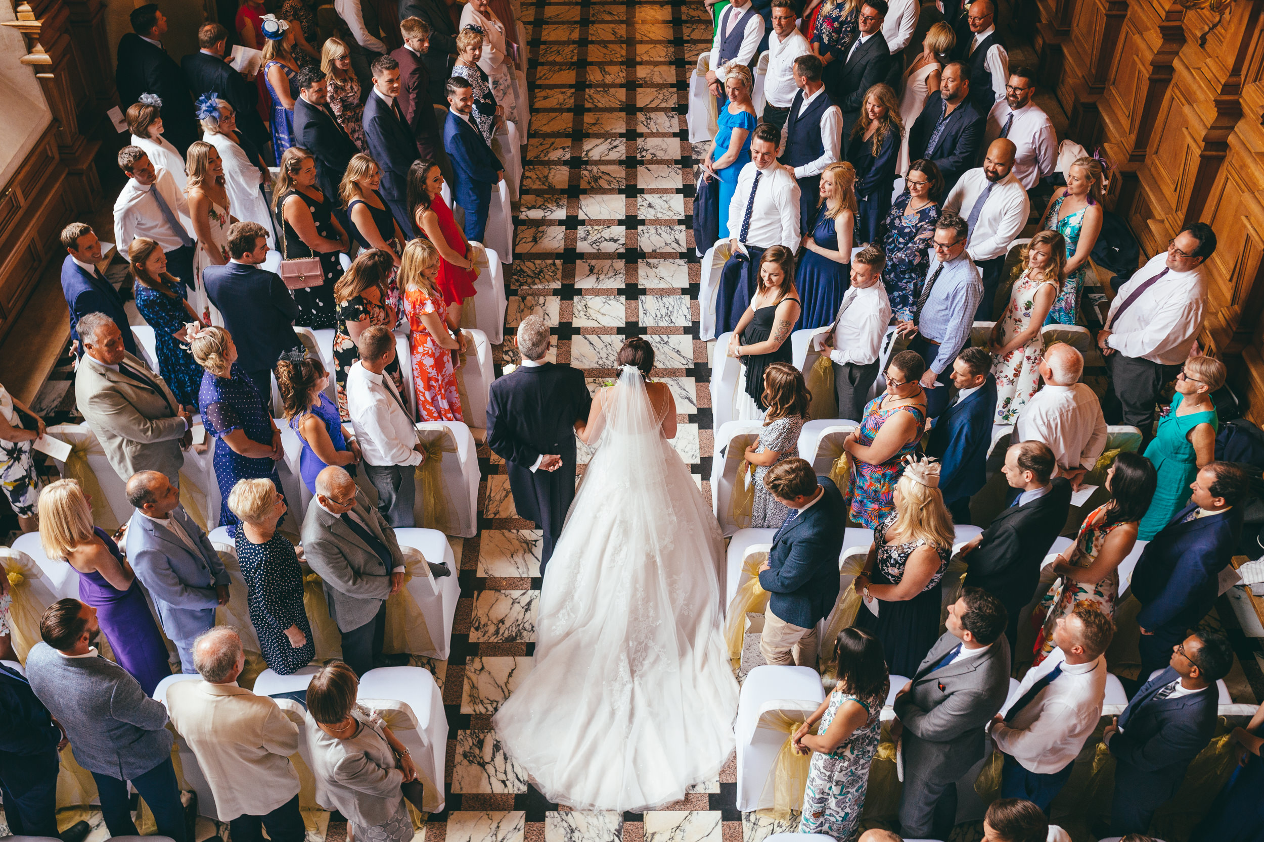 Bride and her father walking down the aisle shot from above at Harlaxton Manor
