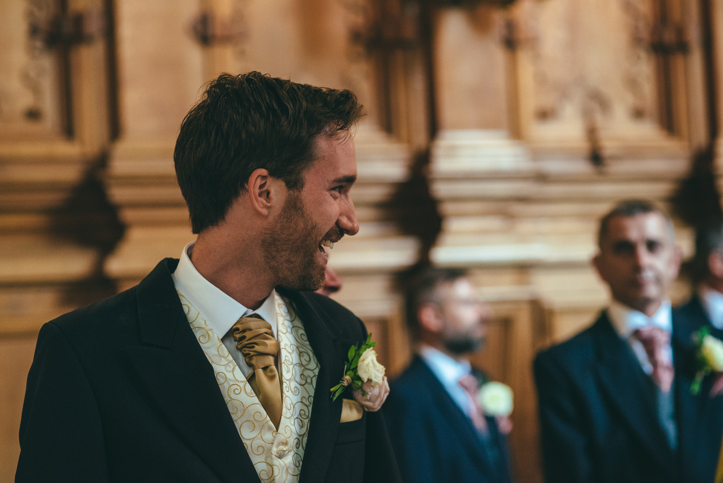 Groom watching his bride walk down the aisle at Harlaxton Manor