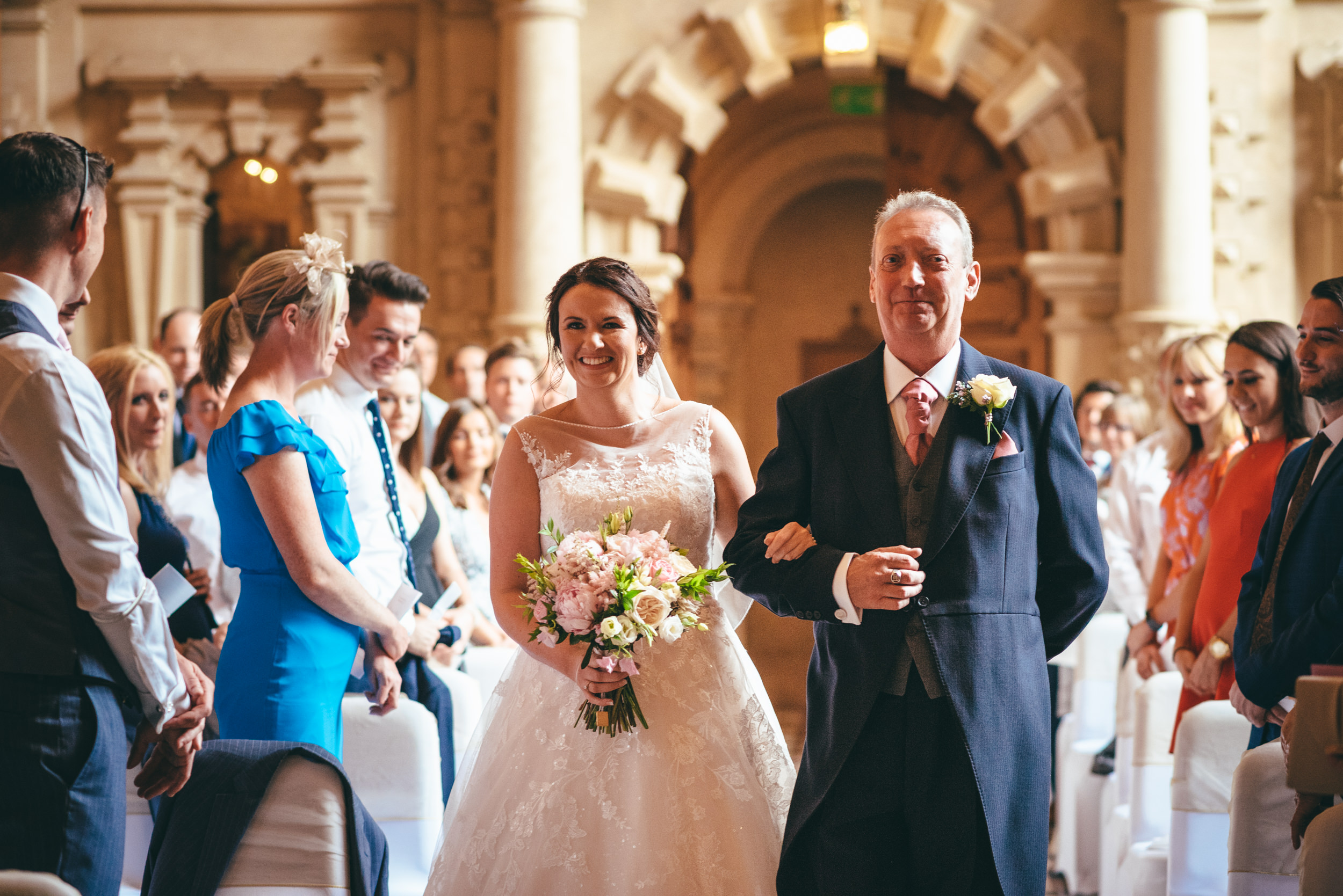 Bride and father walking down the aisle at Harlaxton Manor