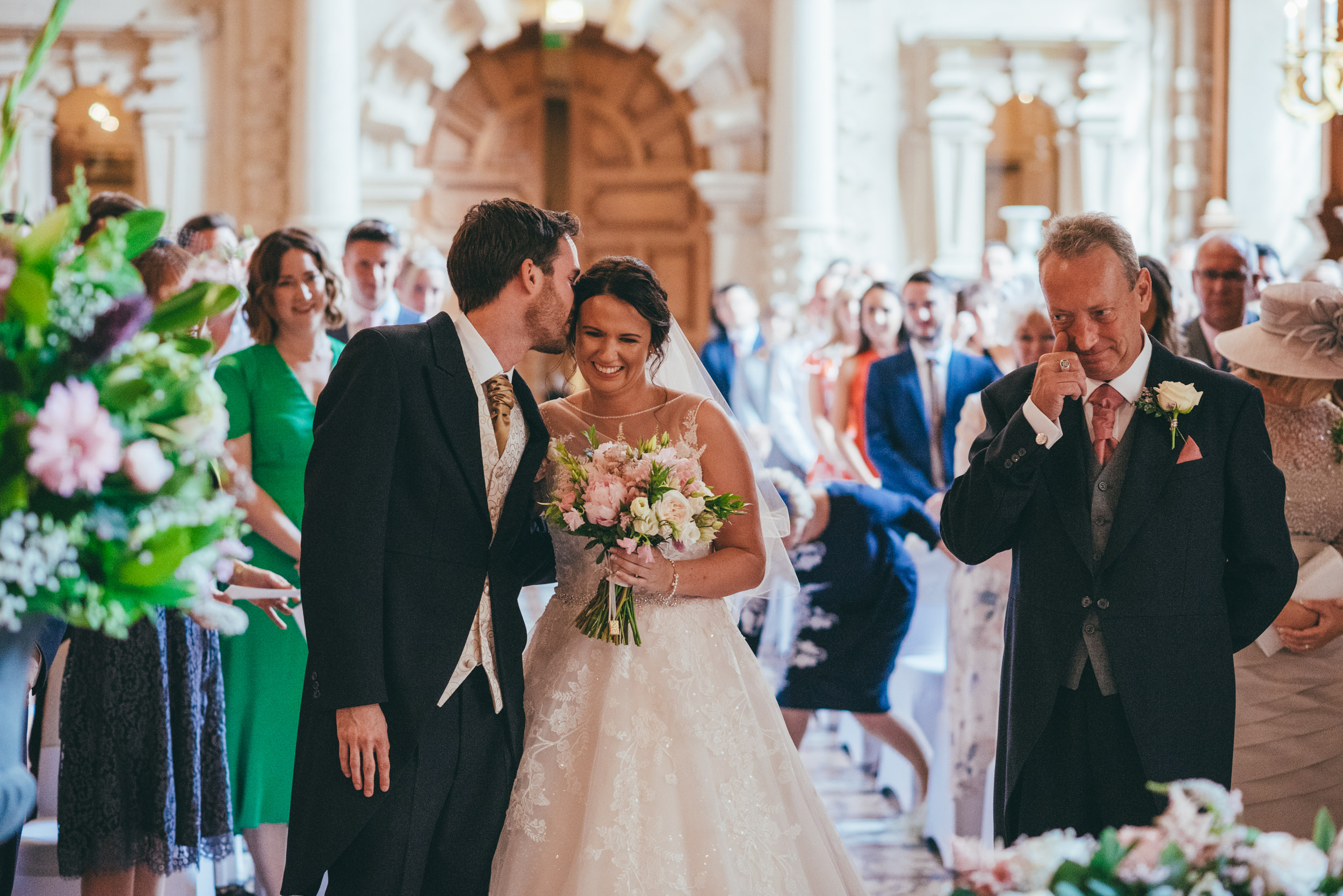 Groom kisses bride on the cheek at Harlaxton Manor