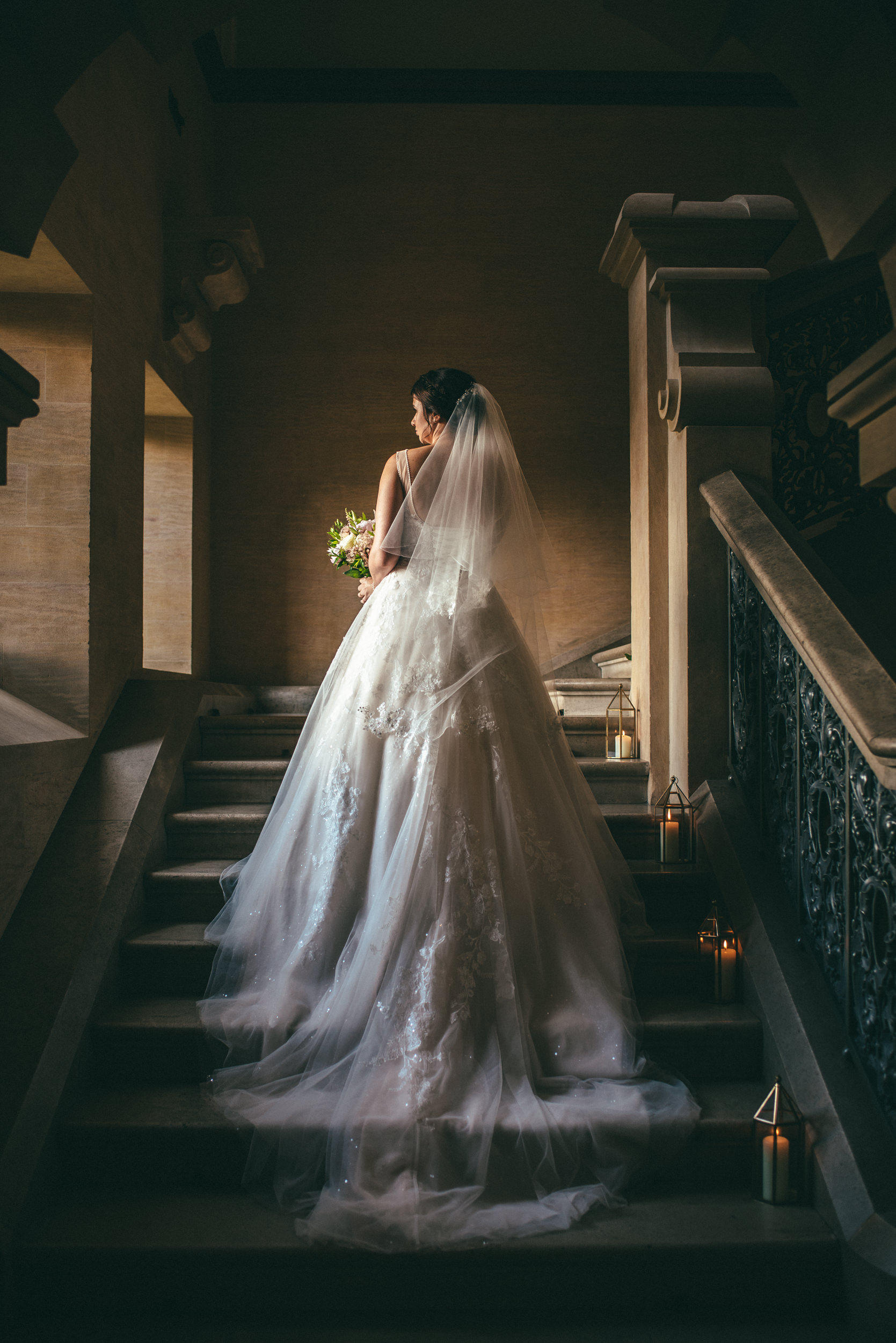 Portrait of the bride on the stairs in natural light at Harlaxton Manor
