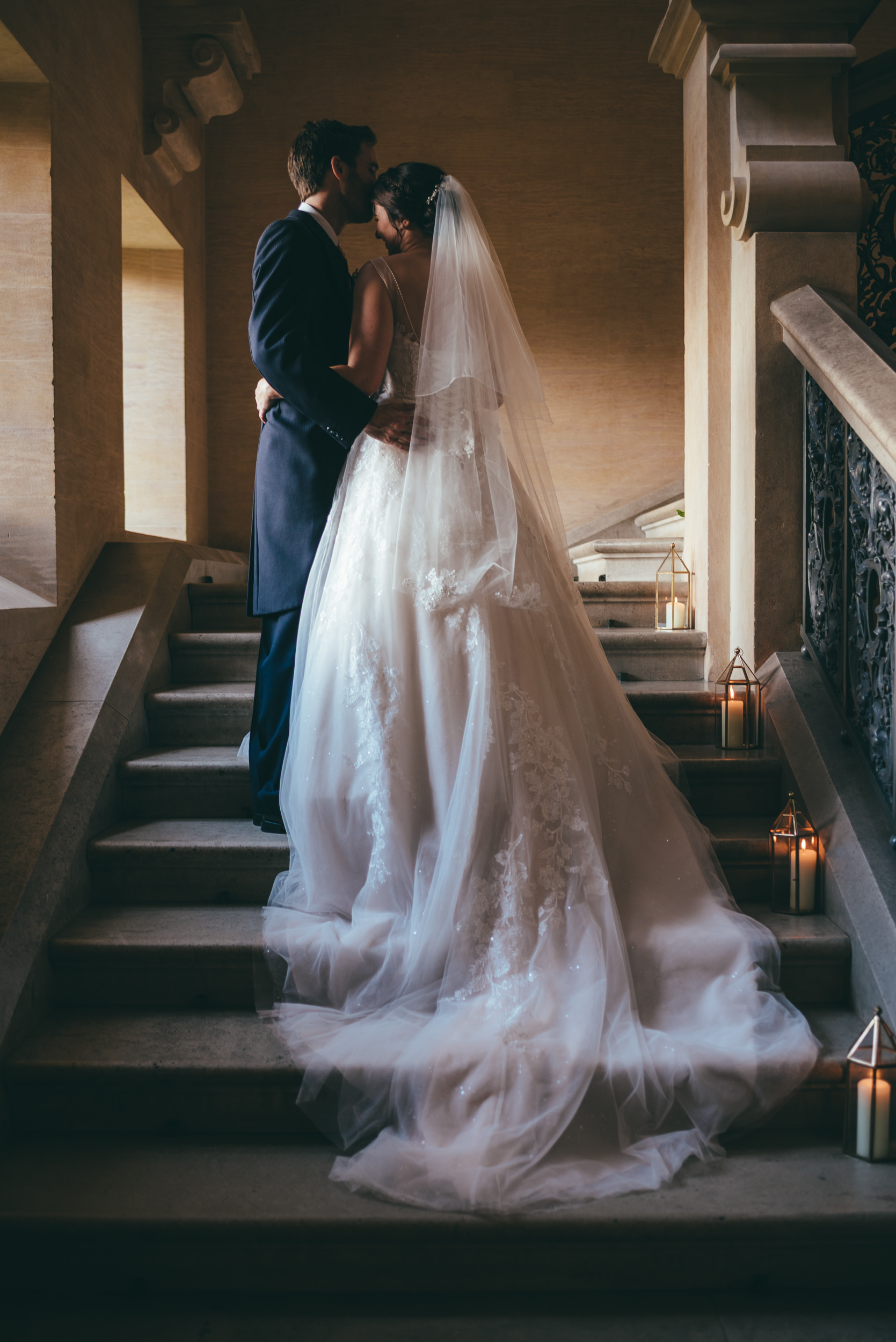 Bride and groom on the stairs at Harlaxton Manor in the window light