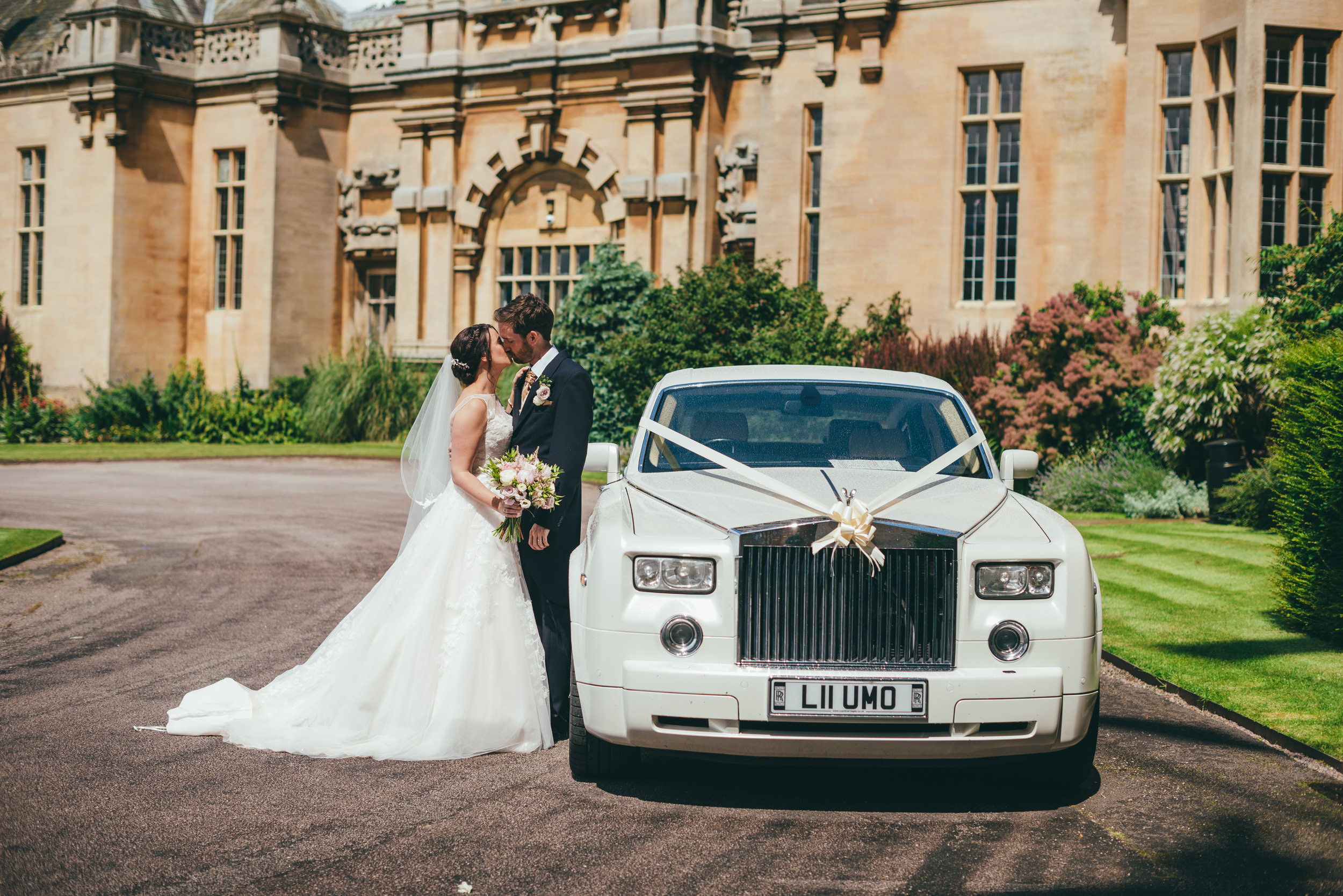 Bride and groom kissing by their Rolls royce wedding car at Harlaxton Manor
