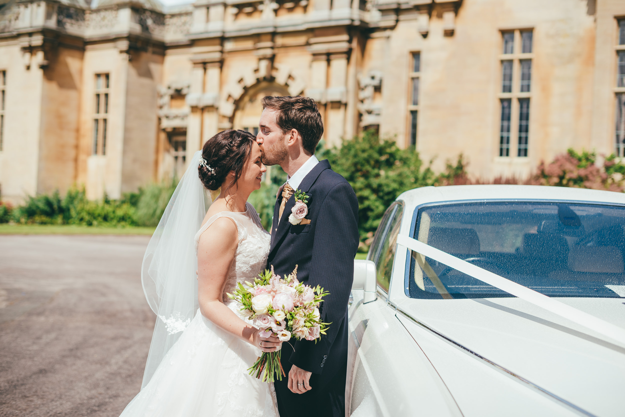 Bride and groom kissing standing next to their Rolls Royce wedding car at Harlaxton Manor