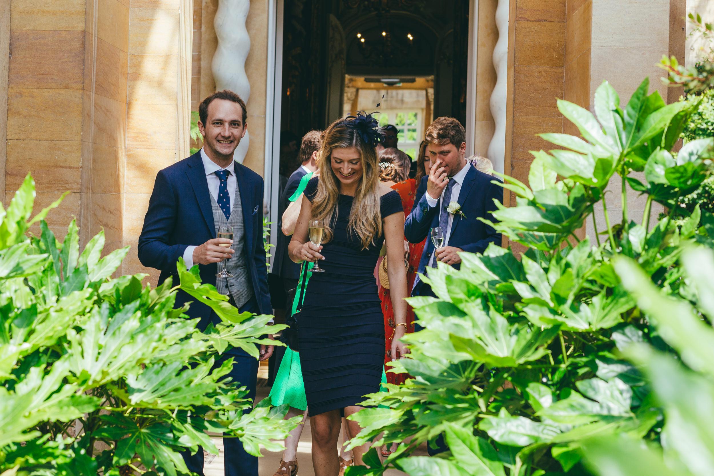 Wedding guests sharing a joke at Harlaxton Manor