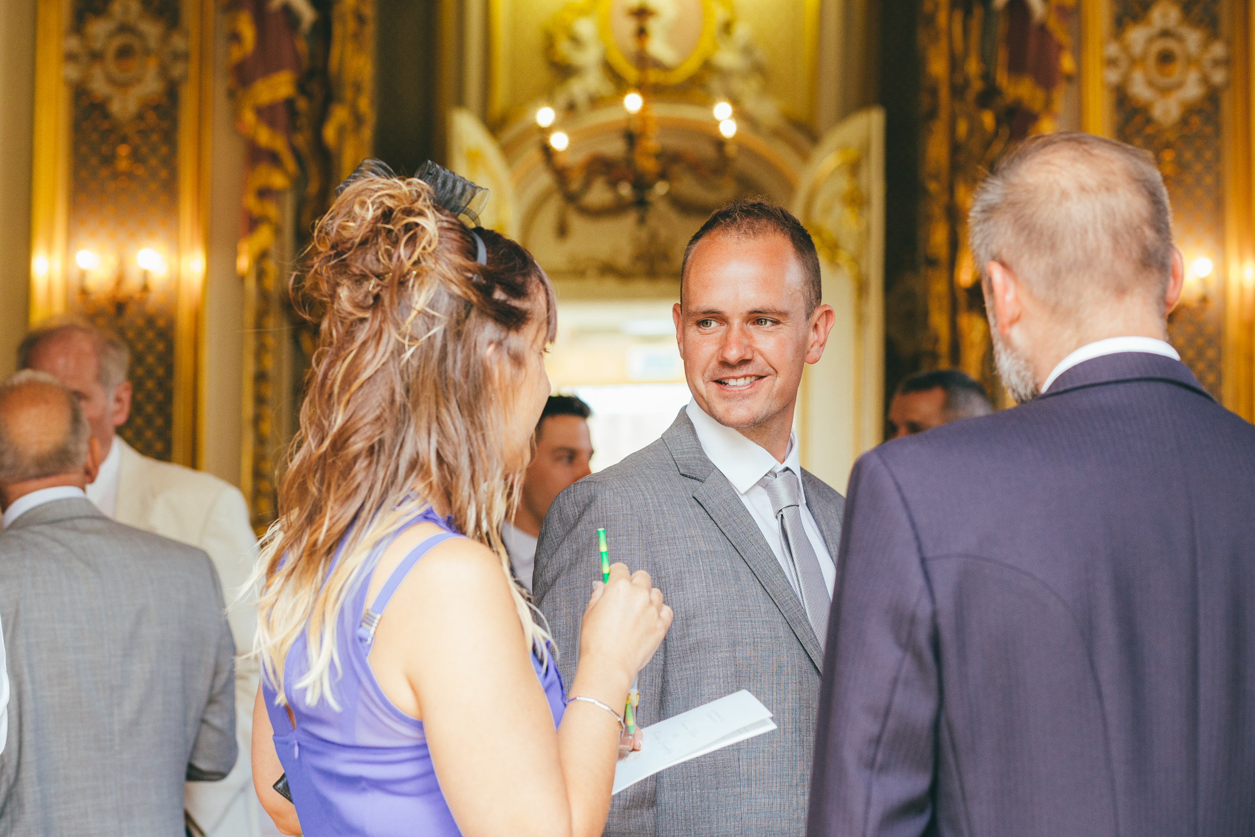 Wedding guests eating canapes and drinking at Harlaxton Manor