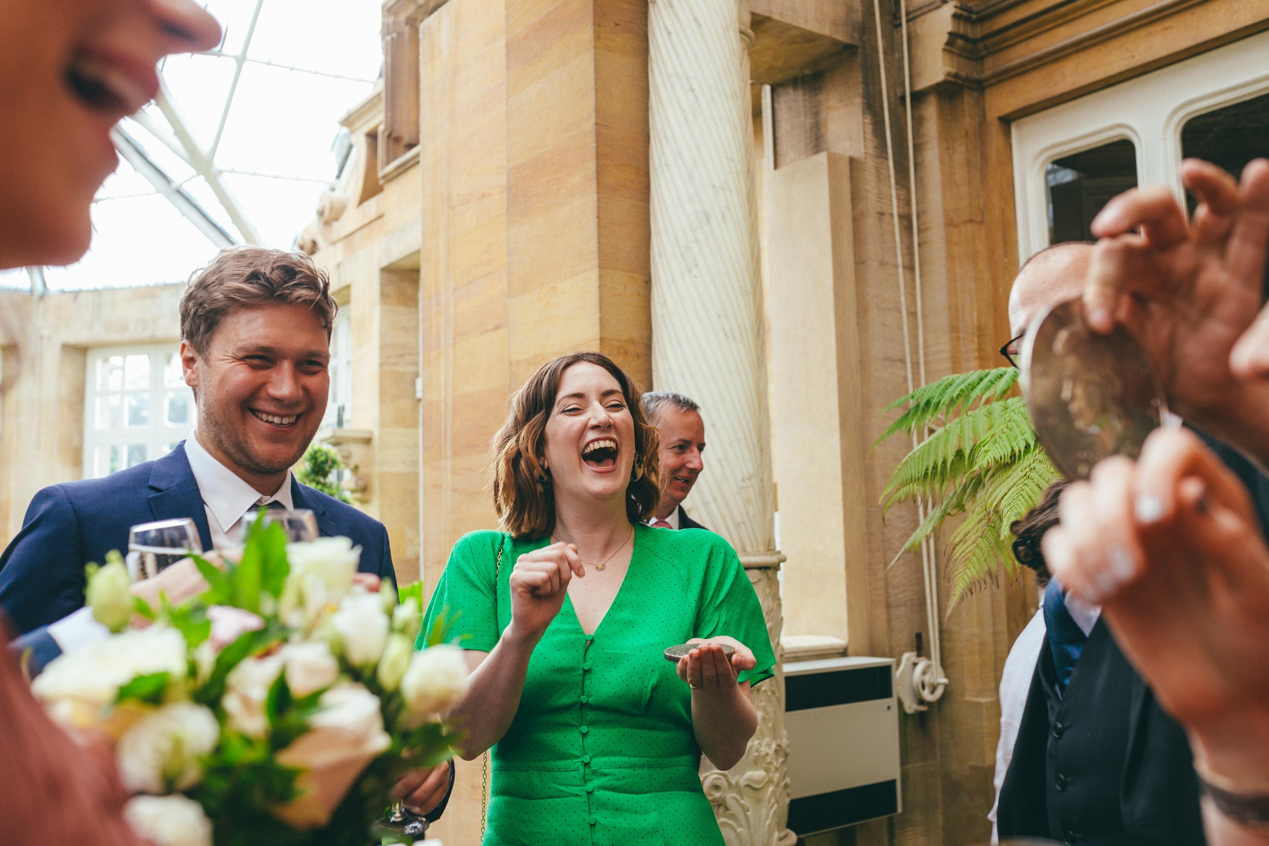 wedding guests laughing at Harlaxton Manor
