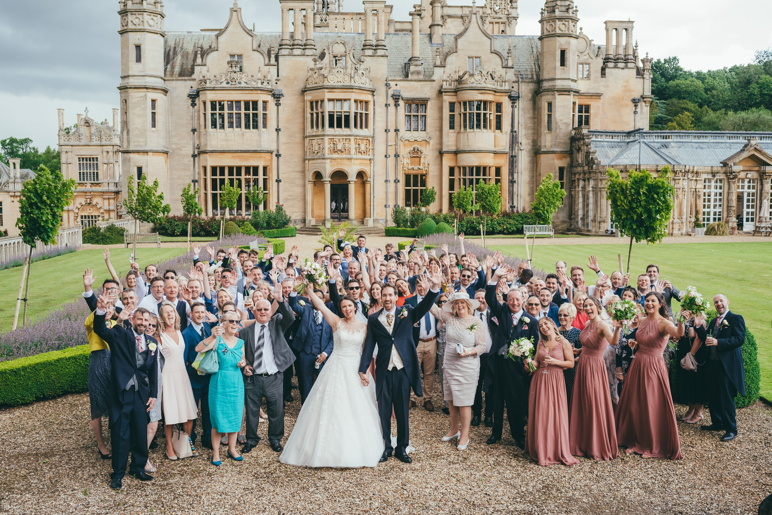 Big group photograph of the wedding guests at Harlaxton Manor