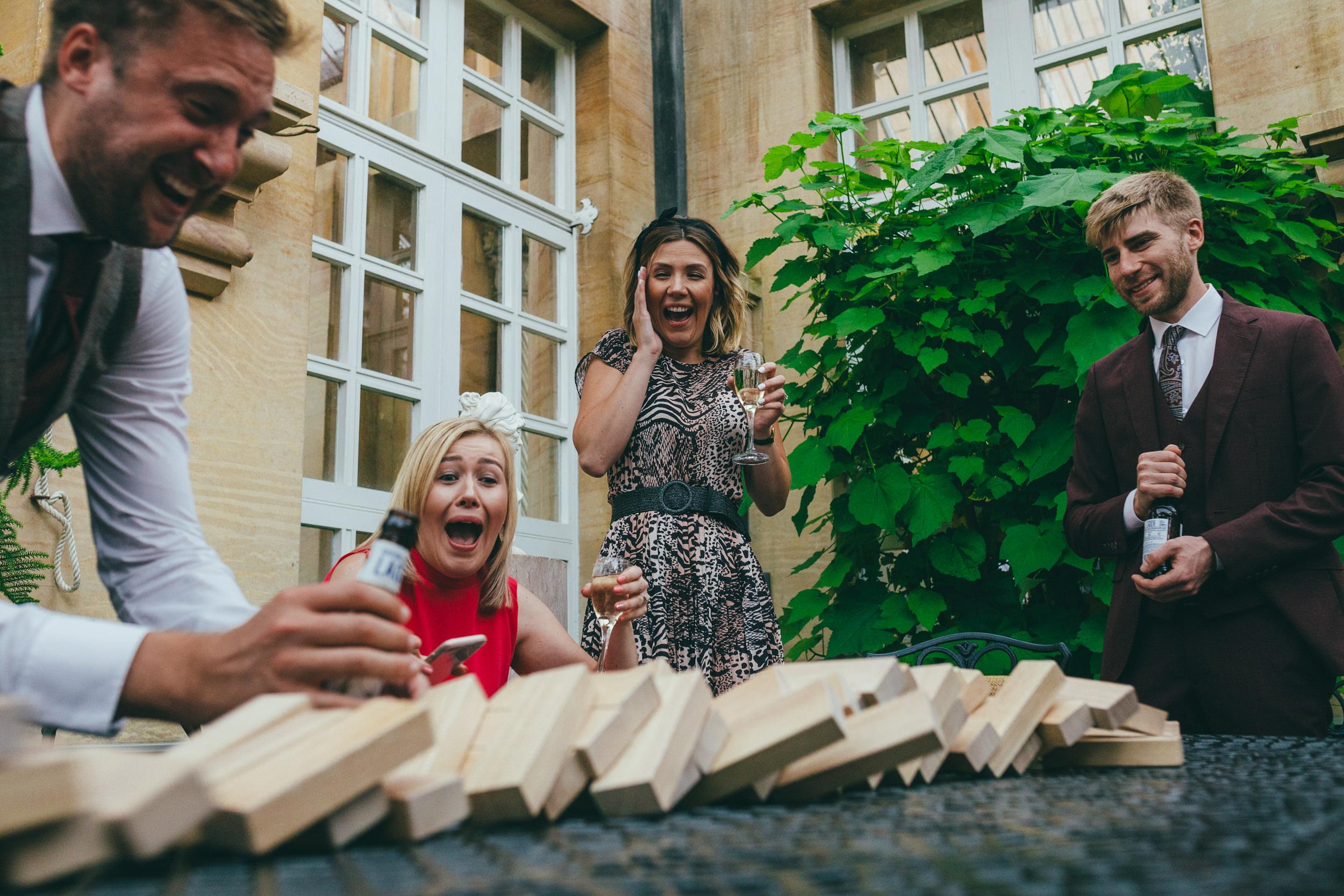 Guests playing Jenga at a wedding at Harlaxton Manor