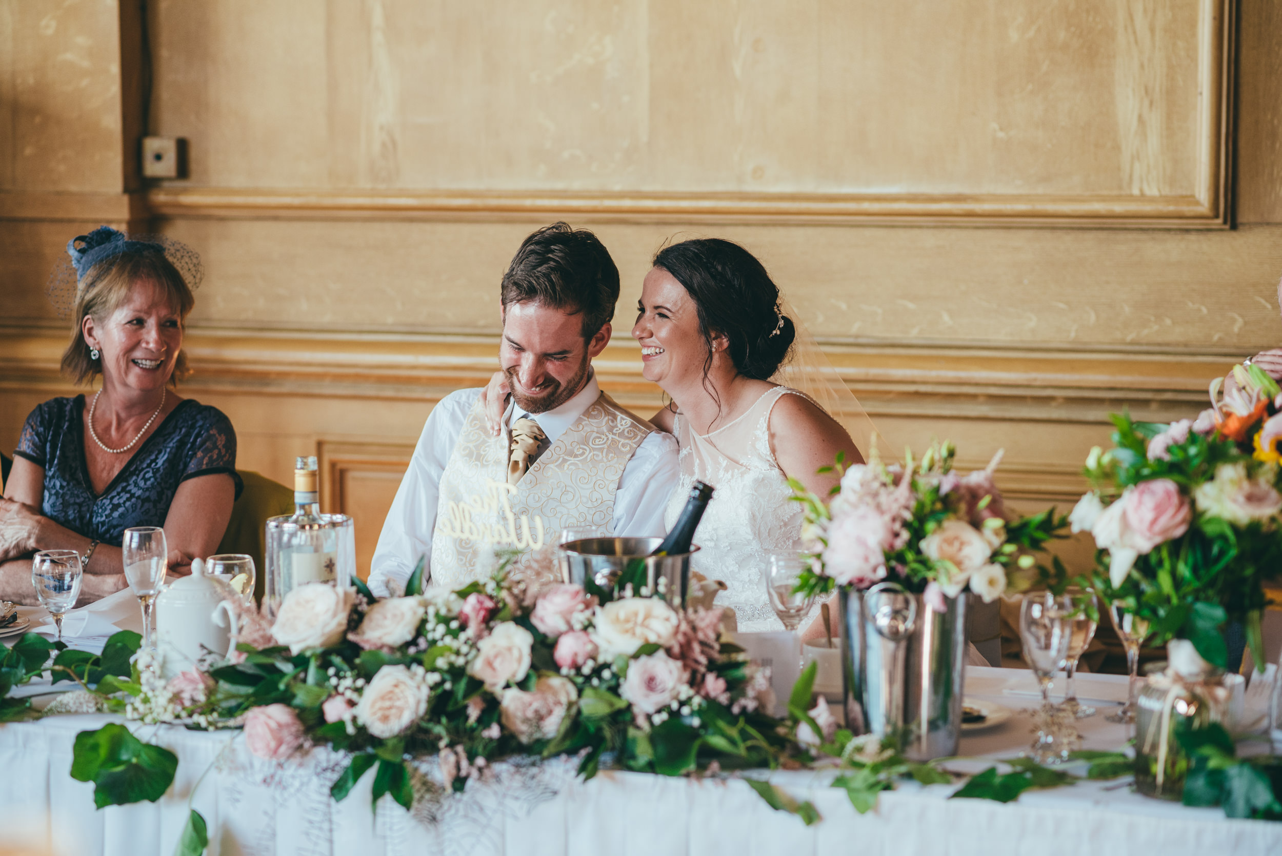 Bride and groom laughing during the speeches at Harlaxton Manor