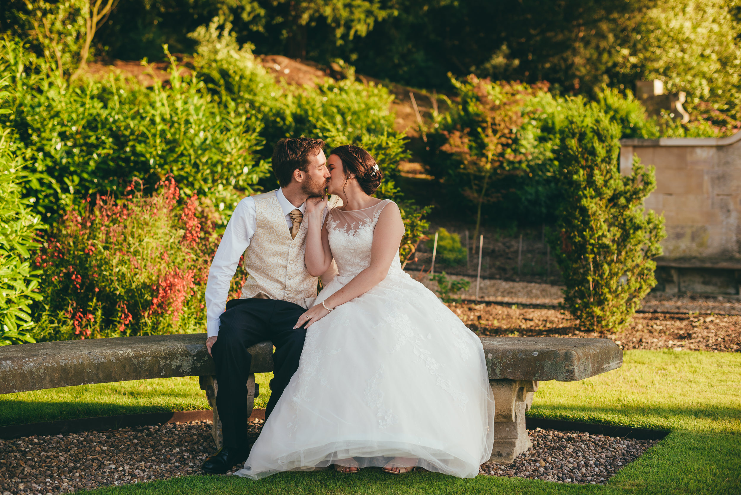 Bride and groom kissing on a bench at Harlaxton Manor