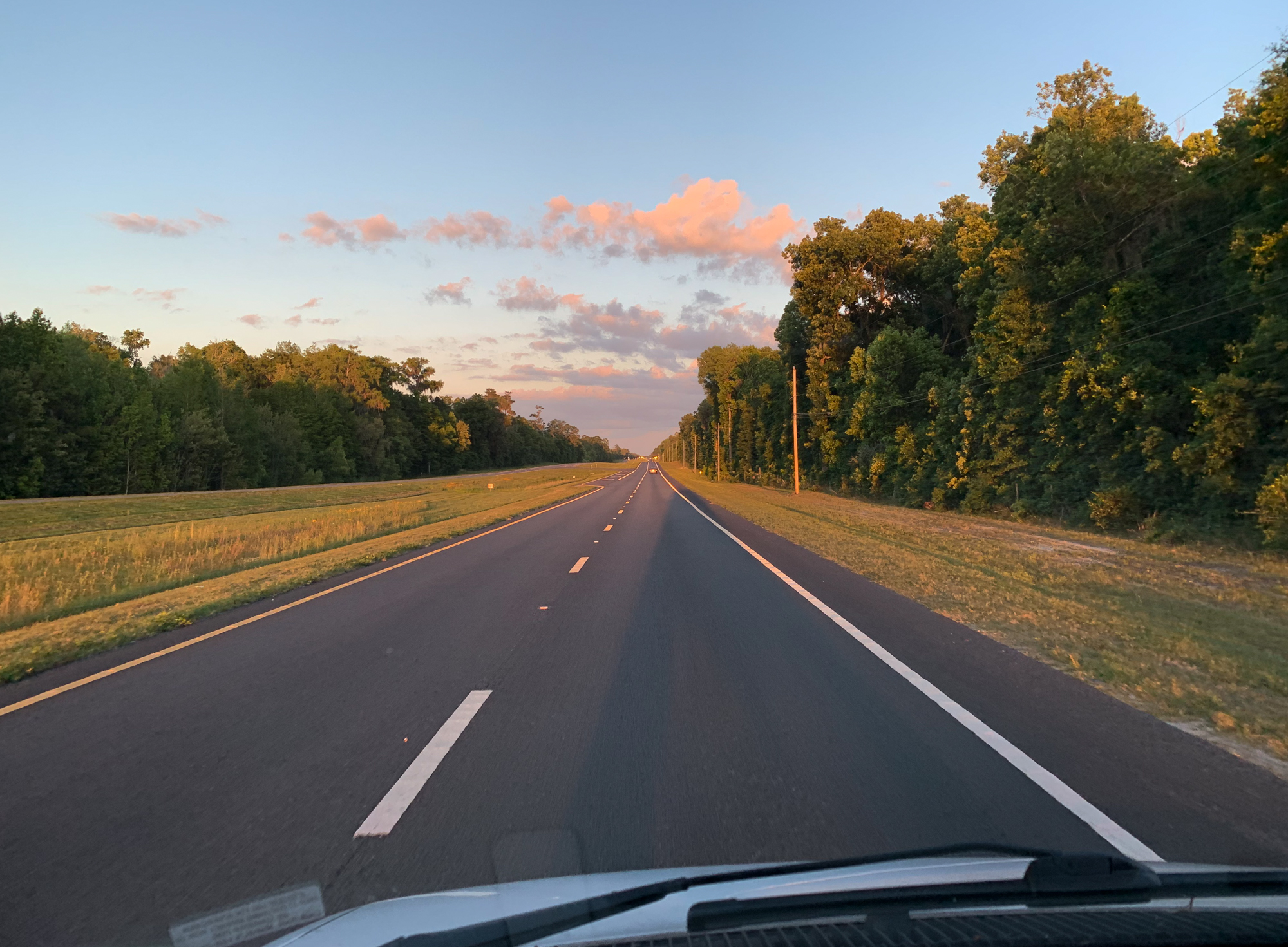 The van casts a long shadow on the highway as the sun goes down. Shot details: iPhone XR