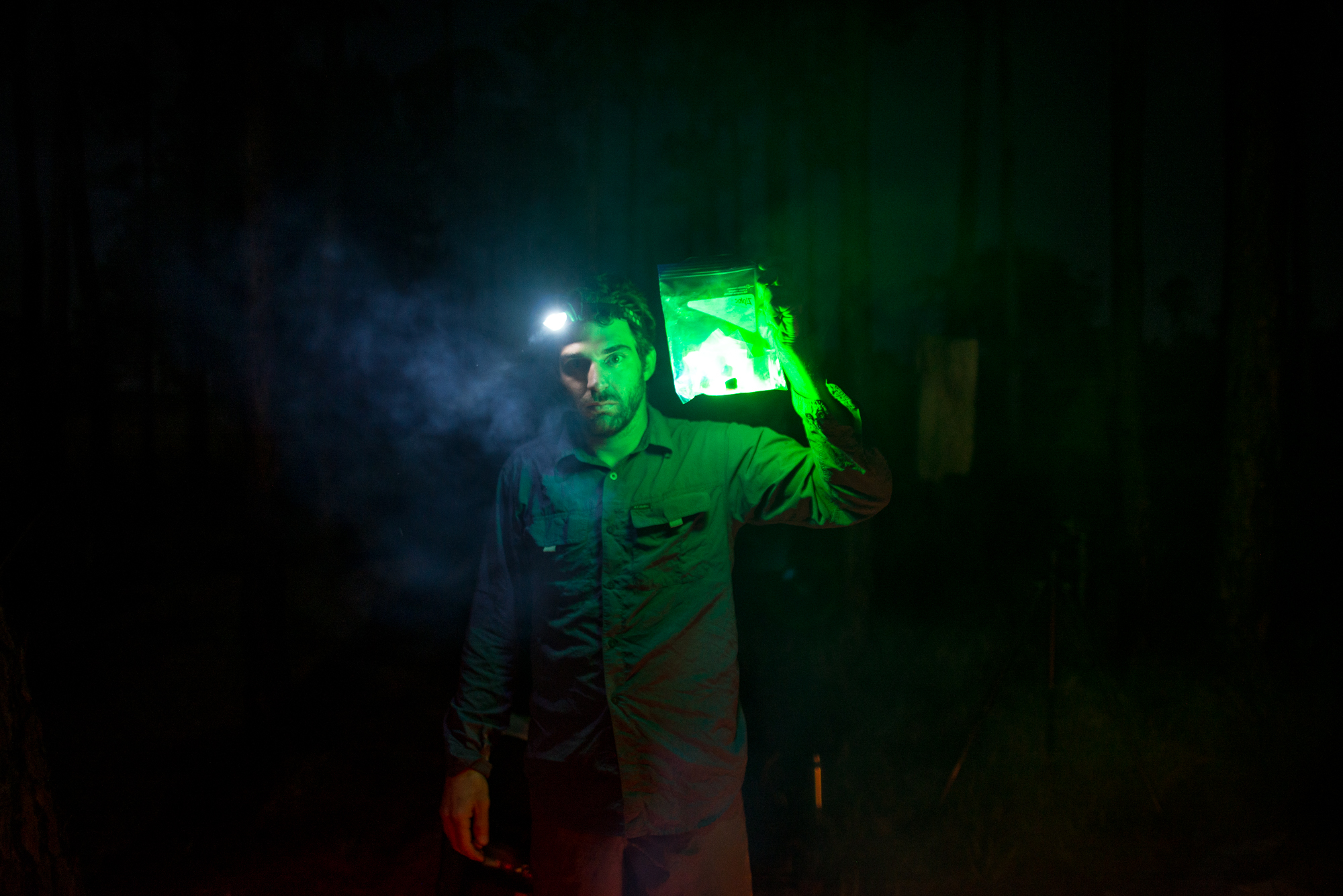 Alex holds a bag of green LEDs to his face for a portrait before getting in the water.