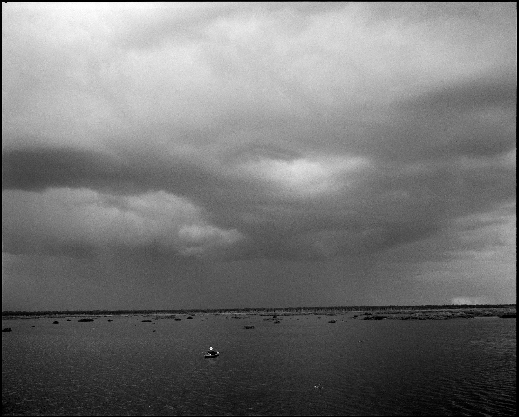 Alex sits in his kayak as a massive thunderstorm sweeps across Paynes Prairie Preserve.