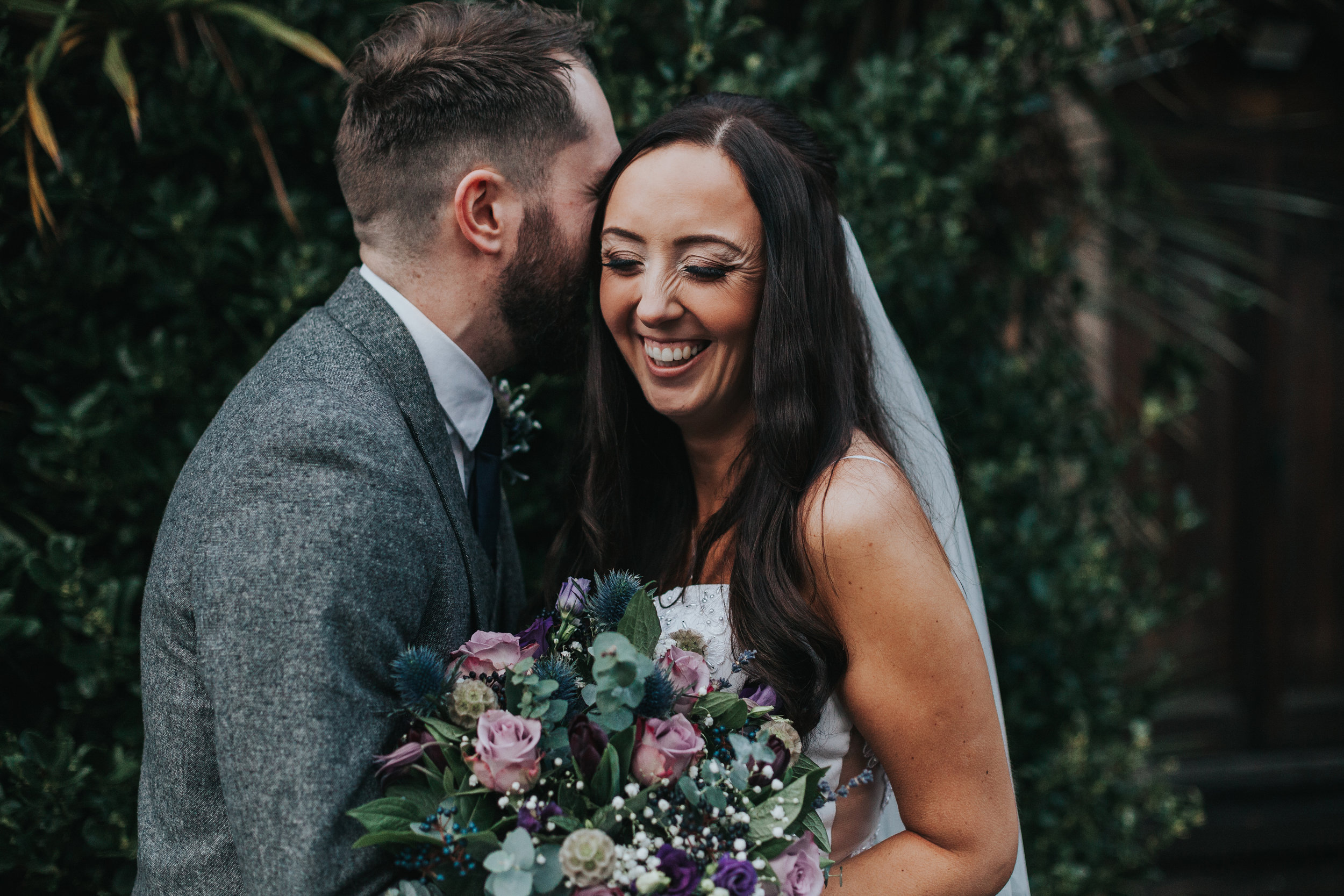 Bride Laughs and Groom Whispers in her ear