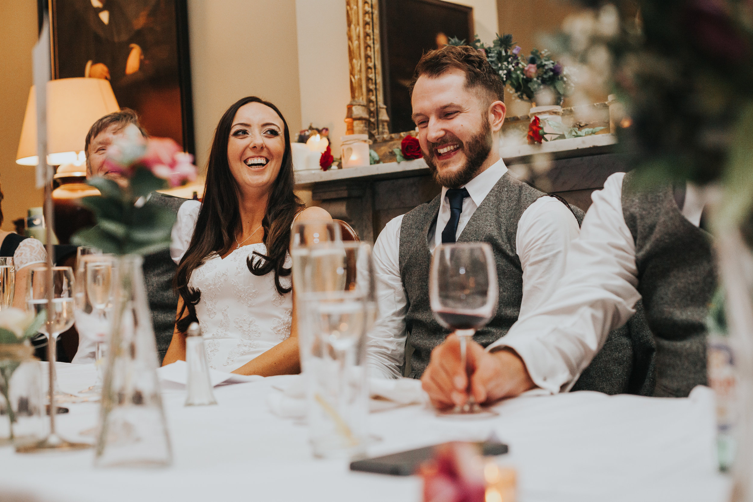 Bride and Groom laughing at Speeches