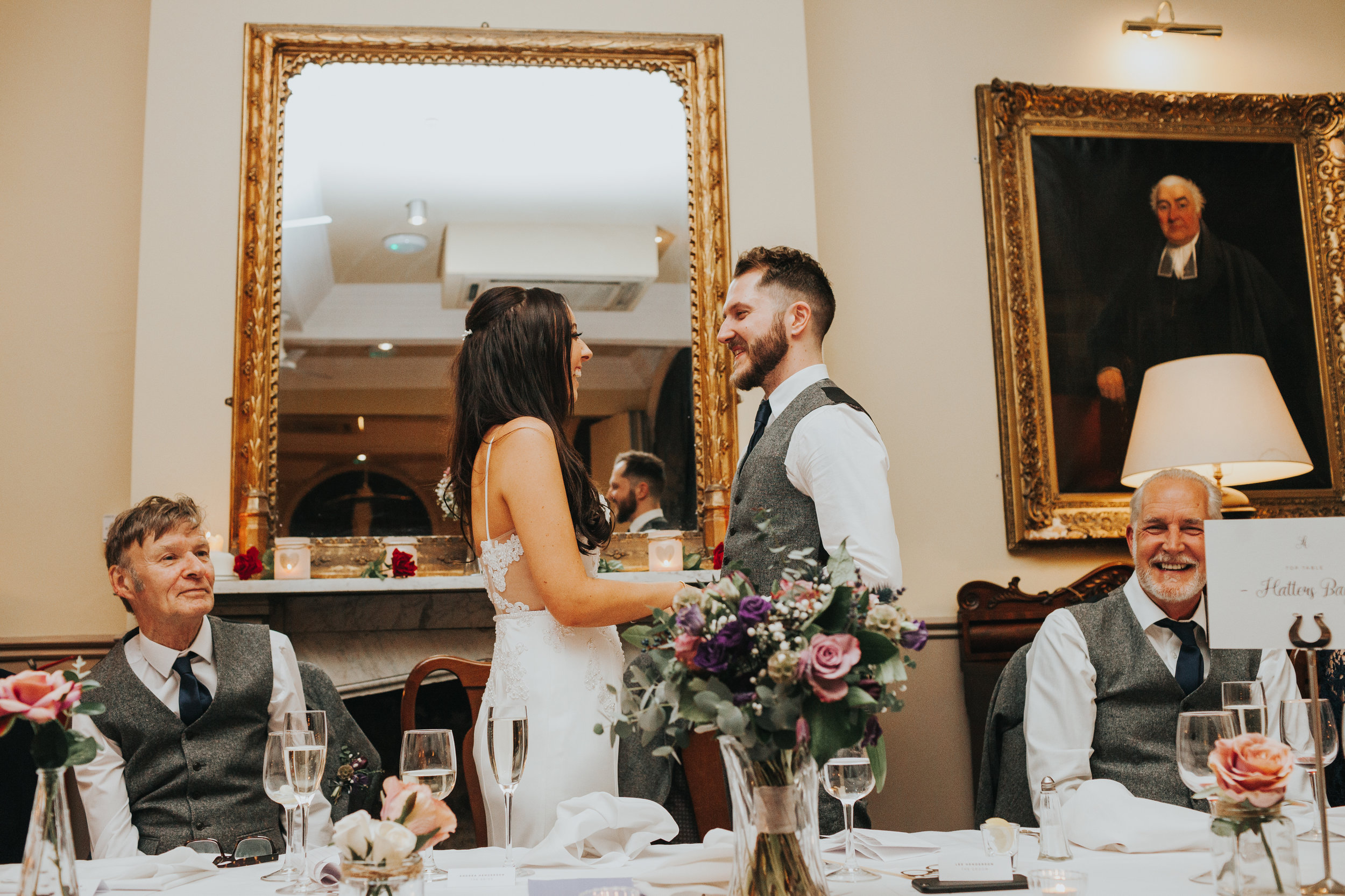 Bride and Groom standing up during best mans speech facing one and other