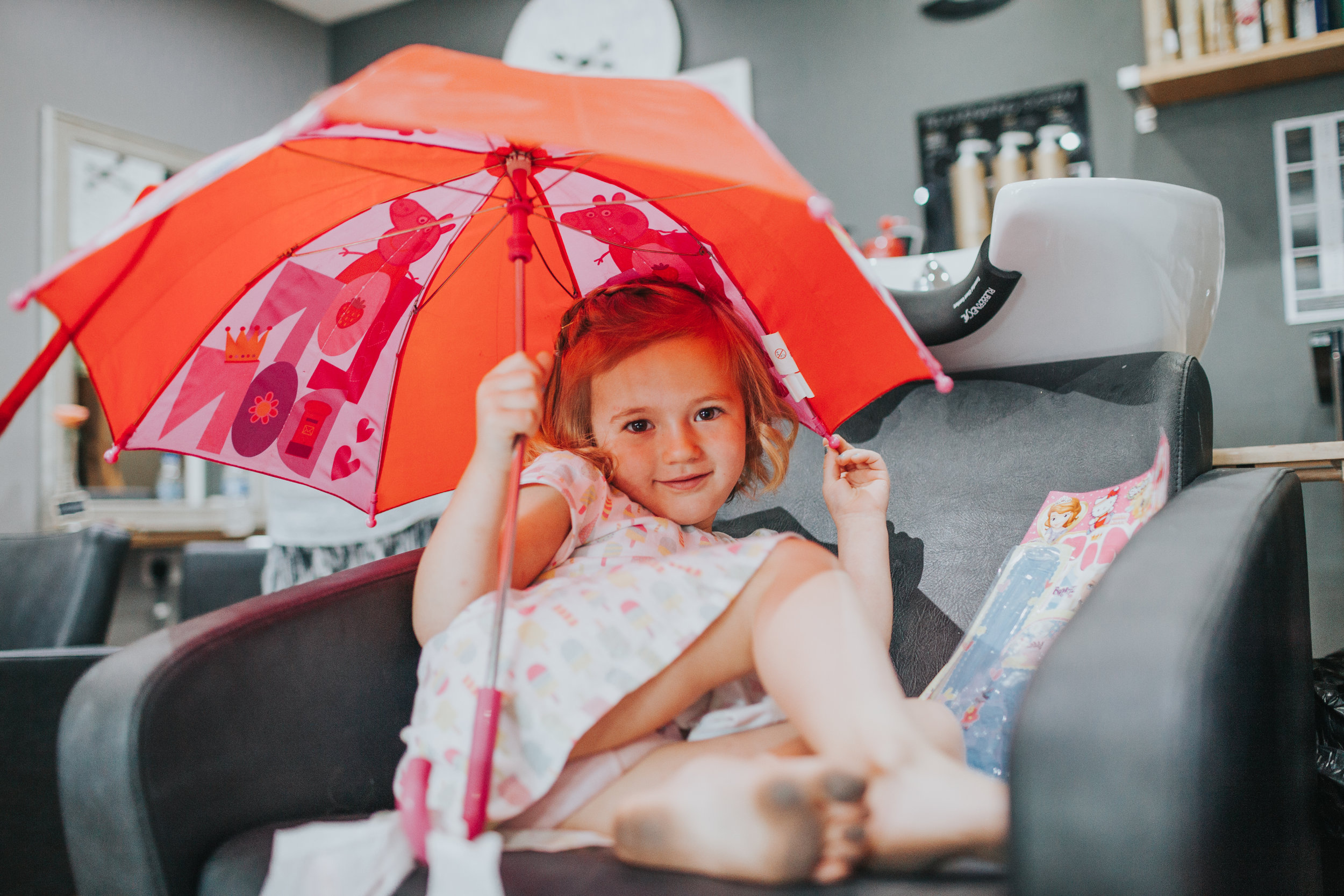 "Previously grumpy child, smiles and plays with hair looking into the camera and showing her blackened feet from running around barefoot. She sits under a red umbrella with total rebellious disregard for ""It's bad luck to open umbrella's indoors rule"". Hero."