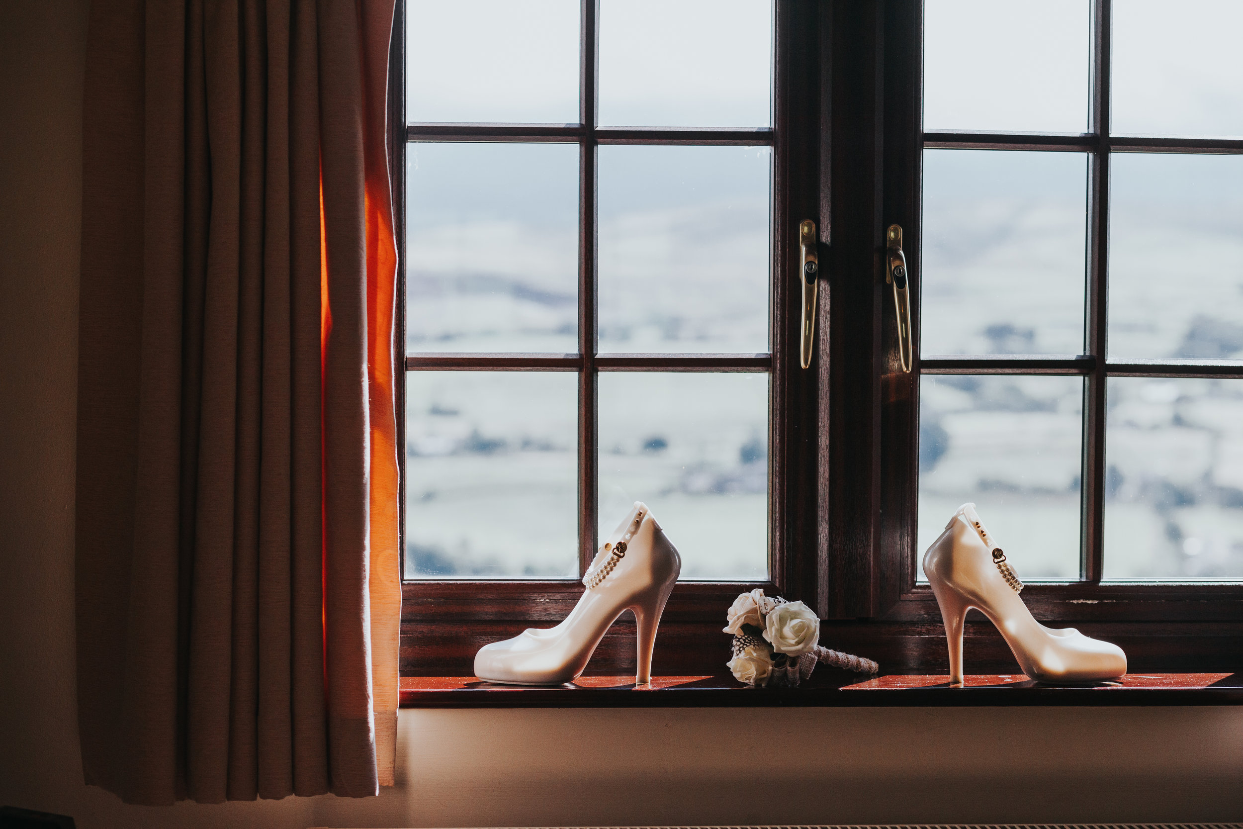 Brides jelly heeled shoes in hotel window, the light coming through them makes them light up like glass slippers, accompanied by chipper child's hand made paper flowers. (Chipper child didn't make them, a professional did)